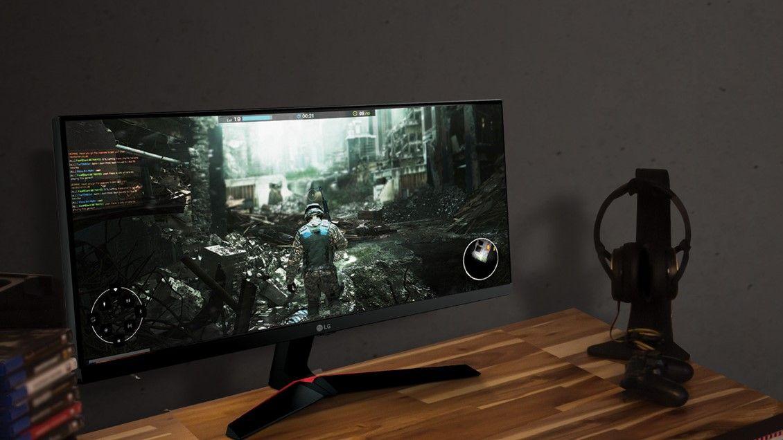 Mesa de madeira com monitor LG ultrawide exibindo jogo de guerra, com controle, headset e um suporte ao lado