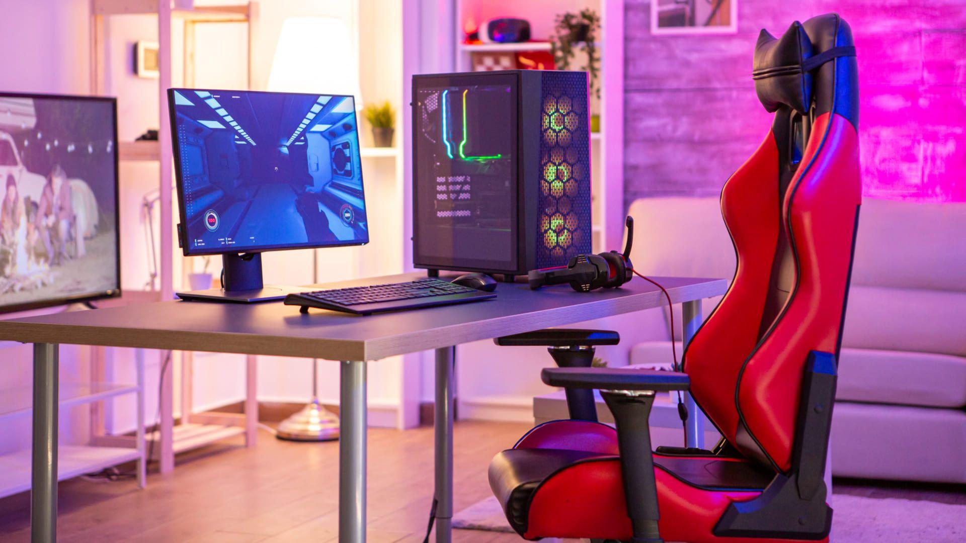 Setup gamer simples com cadeira vermelha, PC gamer com teclado, mouse, monitor e headset, com sofá e TV ao fundo