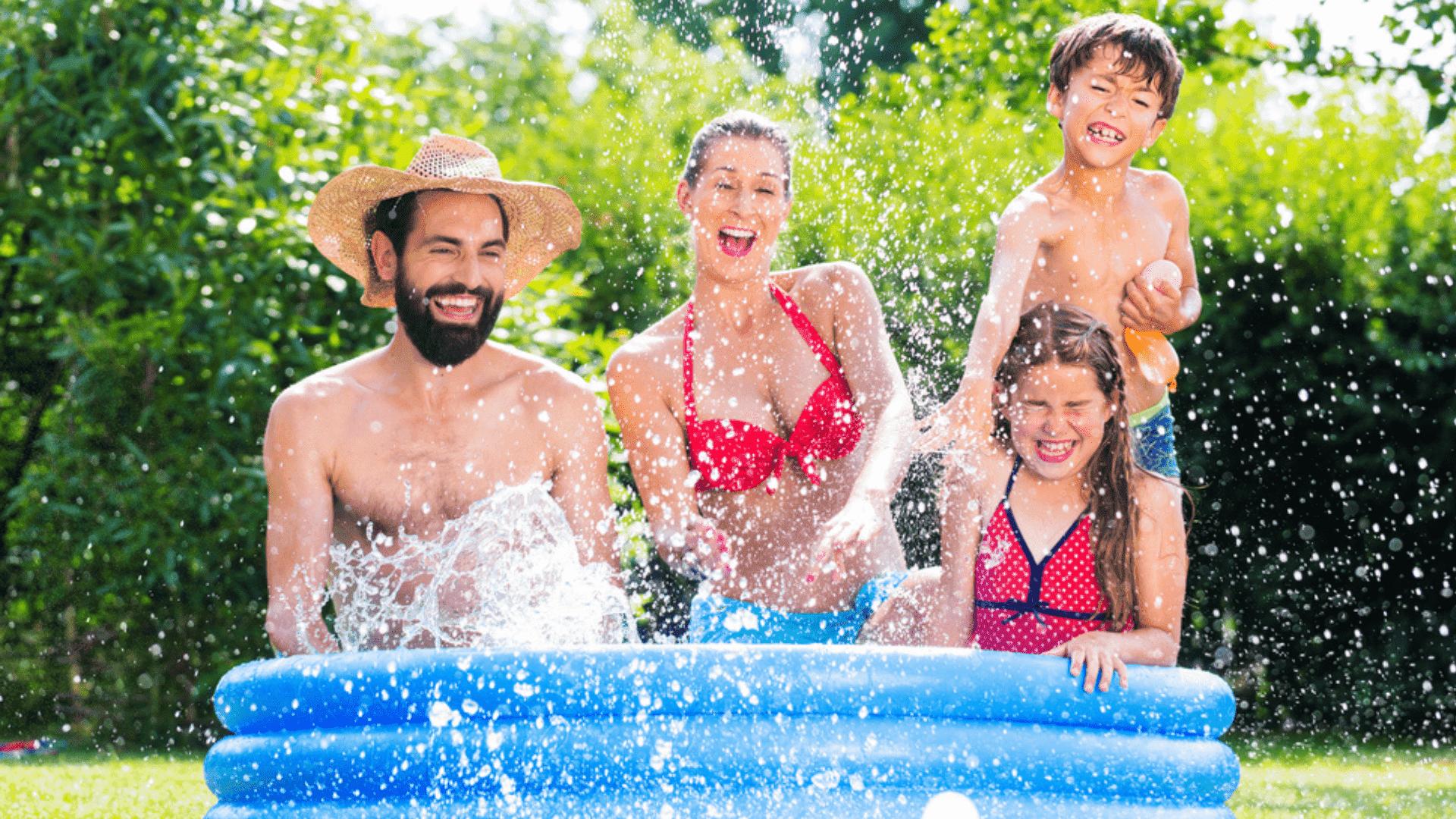 Pai, mãe e irmãos dentro de uma piscina inflável no jardim brincando num dia ensolarado