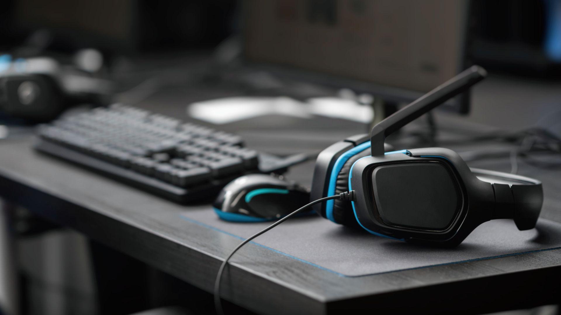 Mesa cinza de quarto gamer mostrando headset, mouse e teclado mecânico da cor preta com detalhes em azul