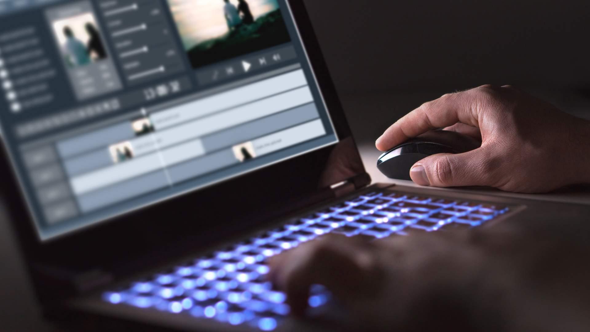 Homem branco usando notebook e mouse com programa de edição em quarto escuro