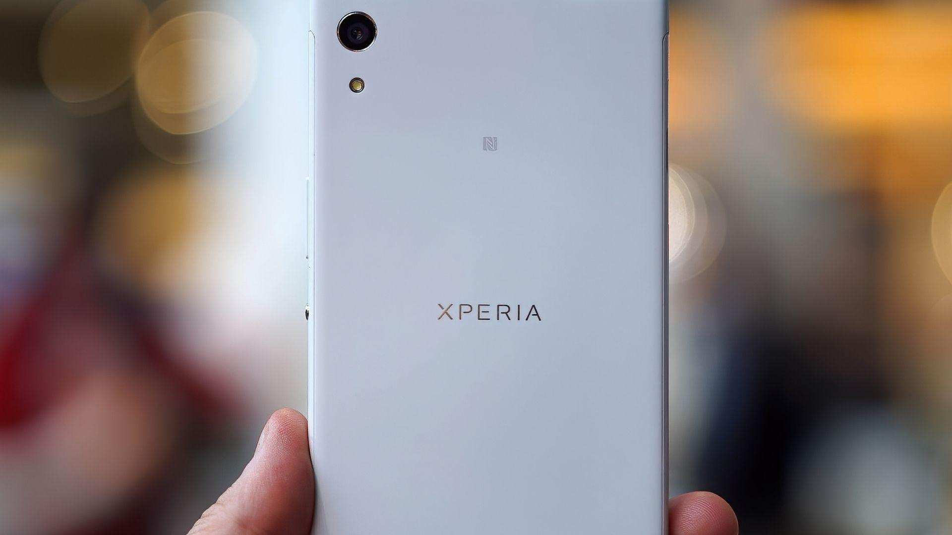 Celular Xperia XA1 branco sendo segurado por dois dedos e em fundo desfocado