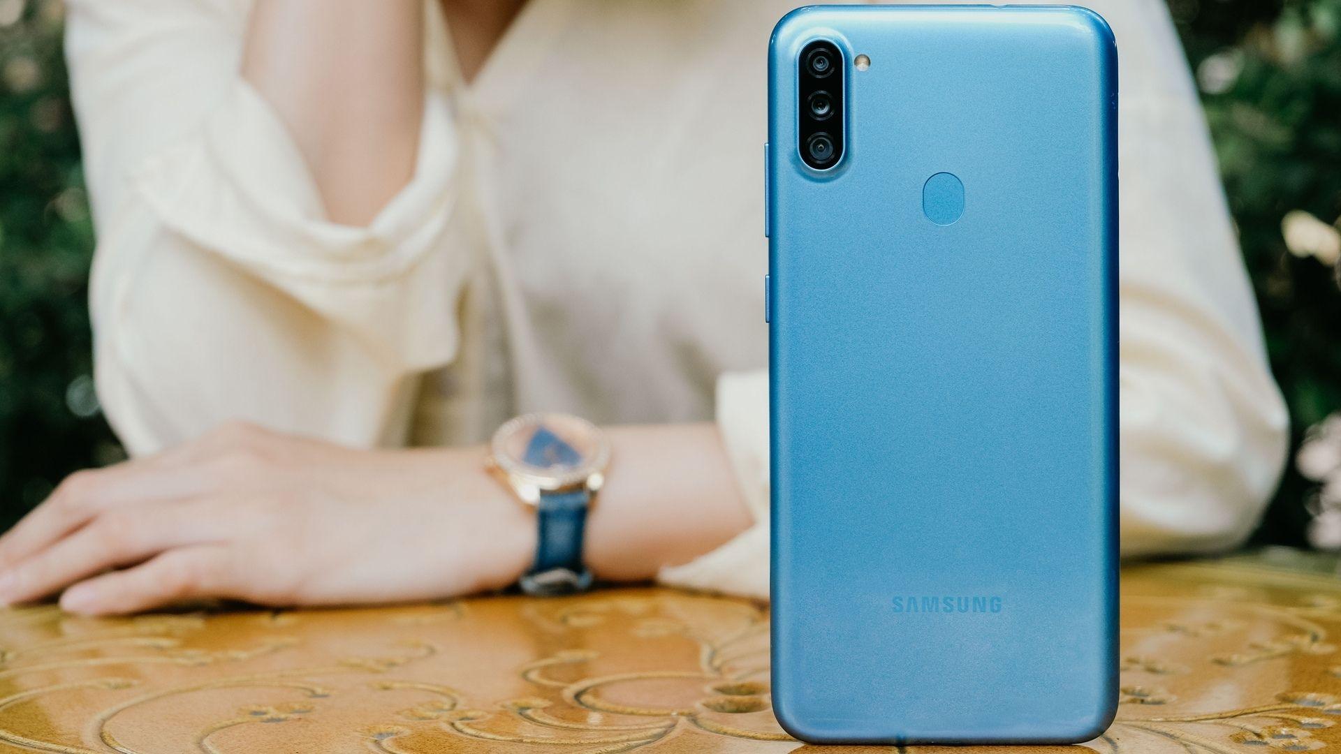 Mãos de mulher apoiadas em mesa com Samsung A11 em primeiro plano na cor azul com traseira destacada