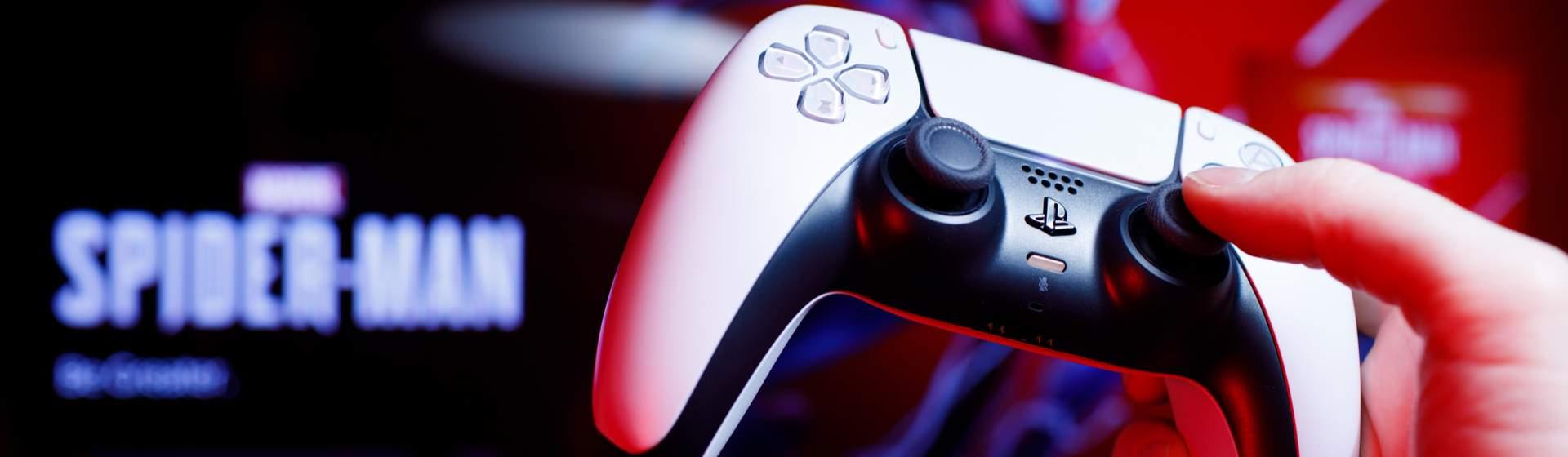 Controle DualSense de PS5 com jogo Marvel's Spider-Man passando ao fundo