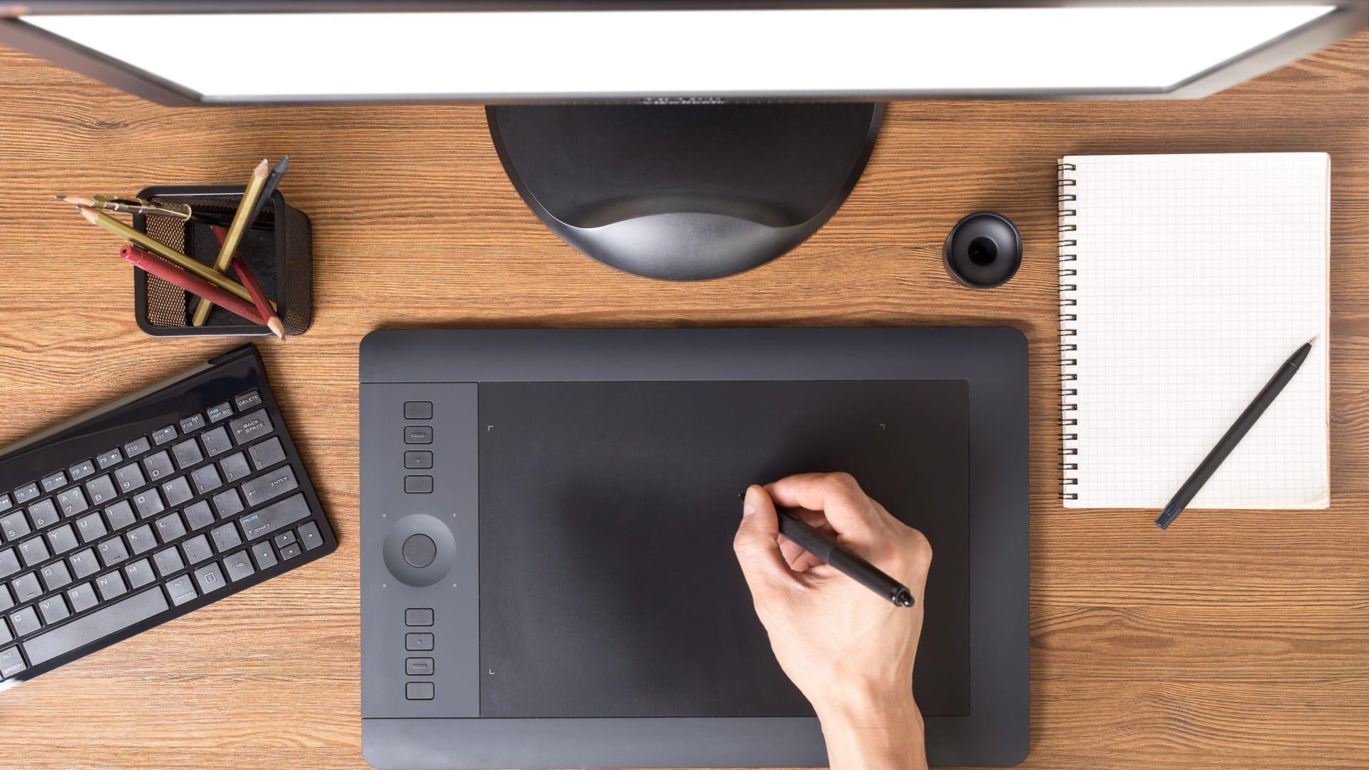 Mesa digitalizadora preta com teclado sobre mesa de madeira com outros acessórios de trabalho próximos