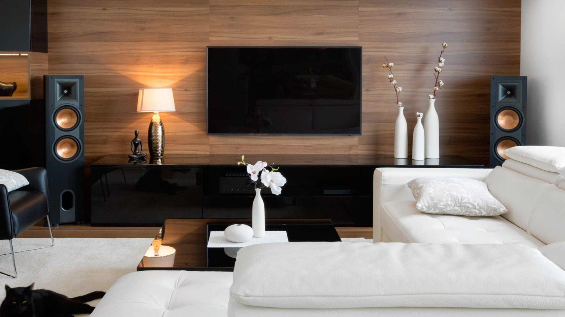 Sala de estar com painel de madeira e TV presa a ele, acima de rack preto
