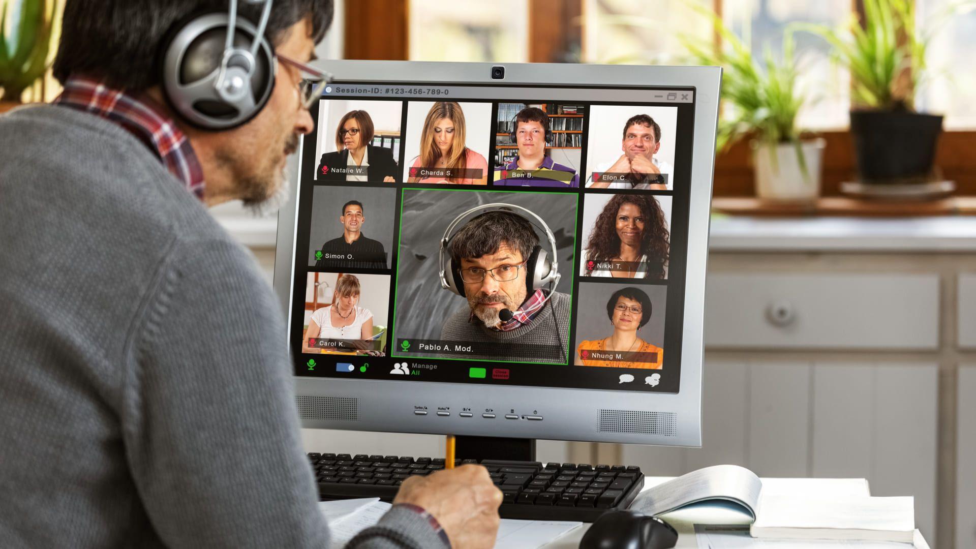 Homem de meia idade de frente para monitor de computador de mesa em videoconferência