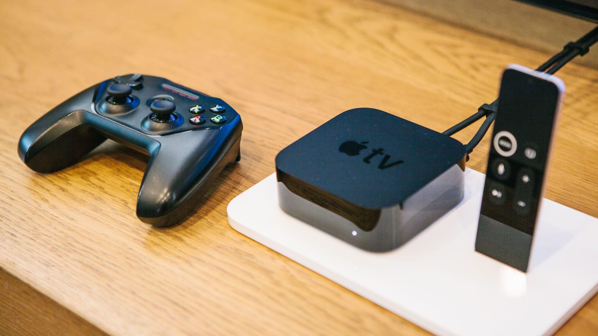 TV box Apple TV e seu controle remoto sobre mesa de madeira