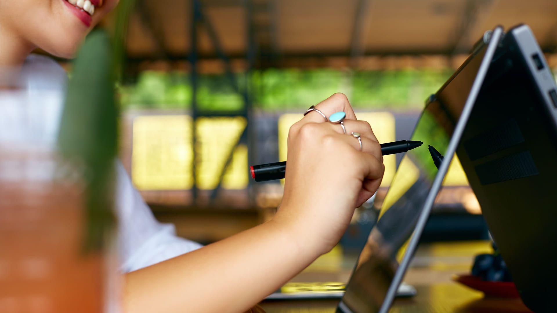 Mulher usando um notebook touchscreen desenhando algo na tela dele com caneta stylus