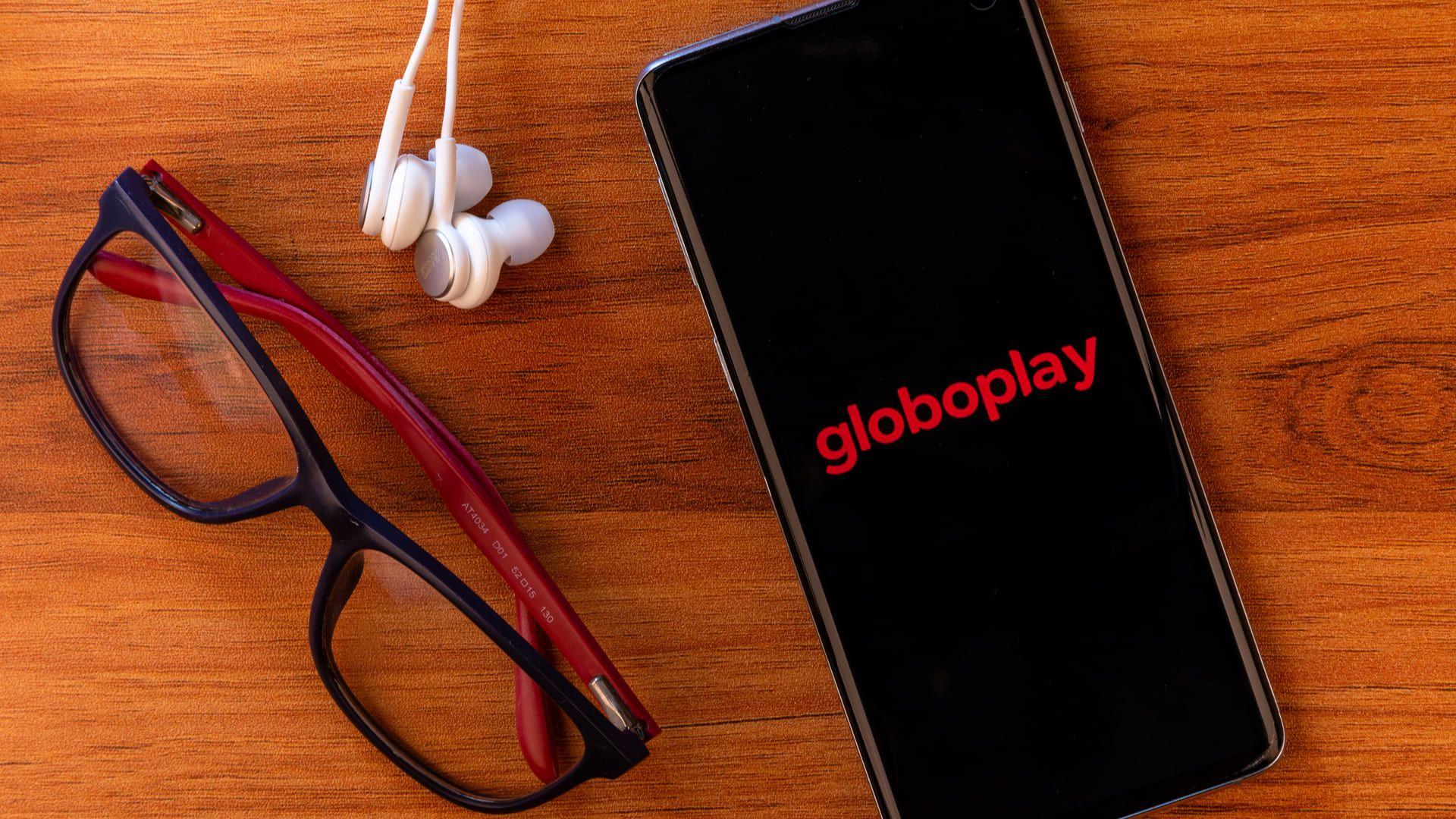 Celular mostrando o logo do Globoplay, um aplicativo para assistir TV, ao lado de um fone de ouvido e um óculos
