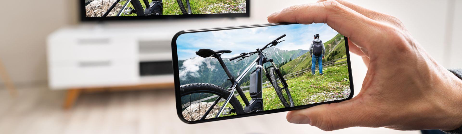 Mão segurando um celular na horizontal com um aplicativo para assistir TV
