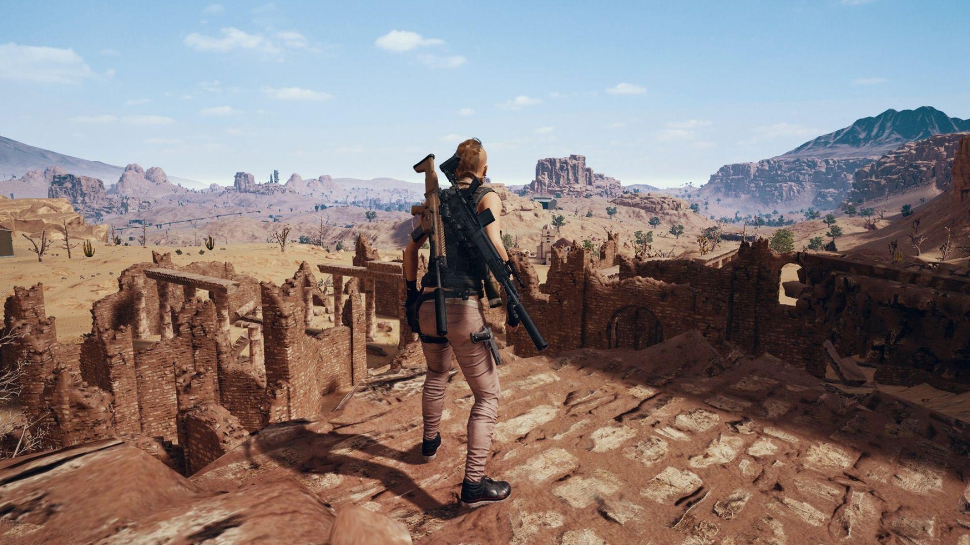 Personagem armada acima de uma ruína observando um cenário desértico
