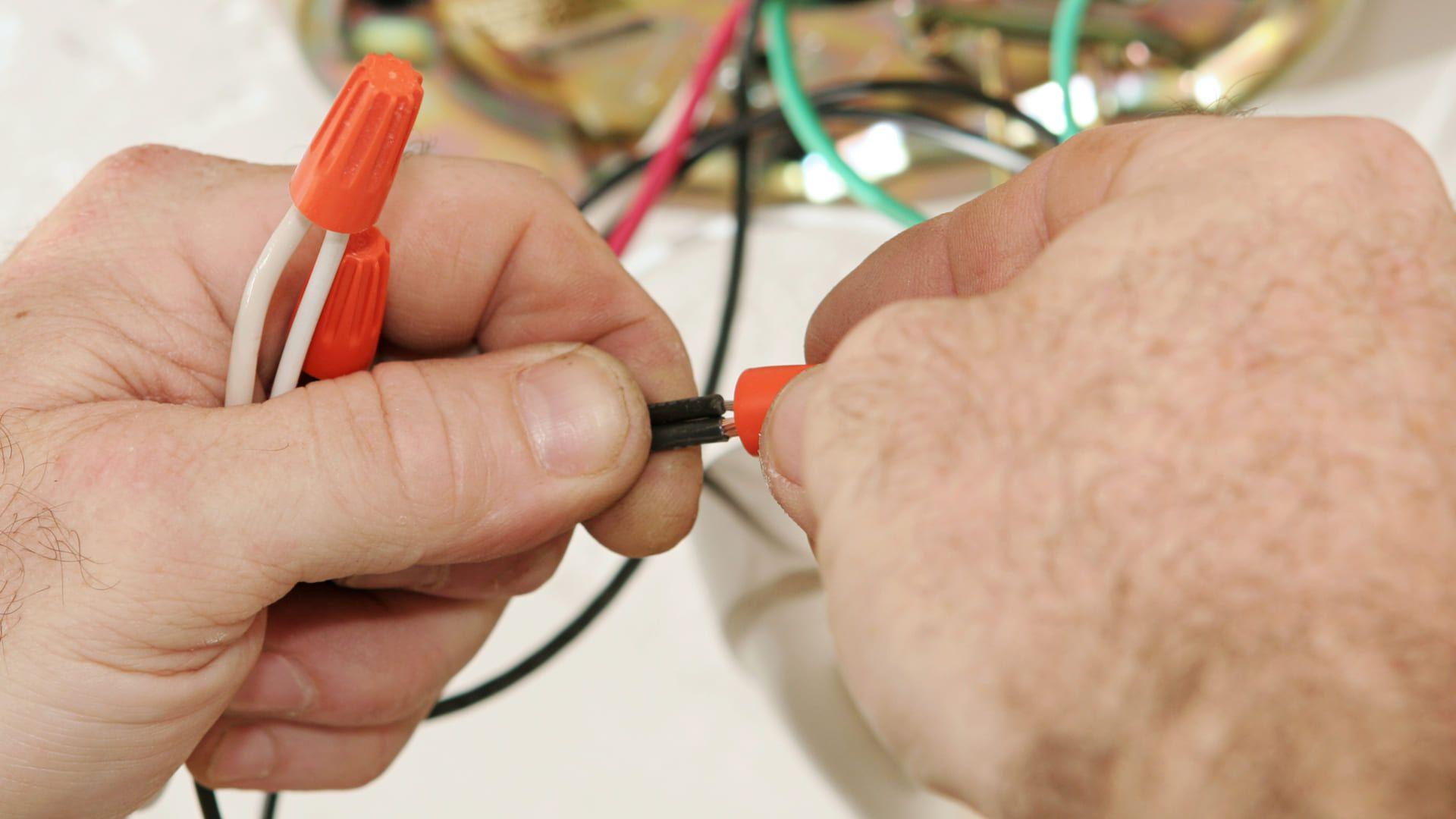 Duas mãos de homem branco instalando cabos elétricos de um ventilador
