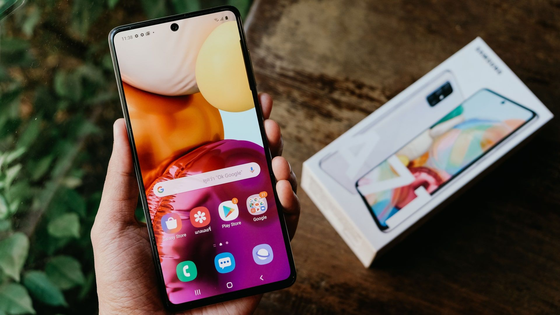 Imagem mostra mão segurando Samsung A71, com caixa do celular ao fundo e em cima de uma mesa de madeira