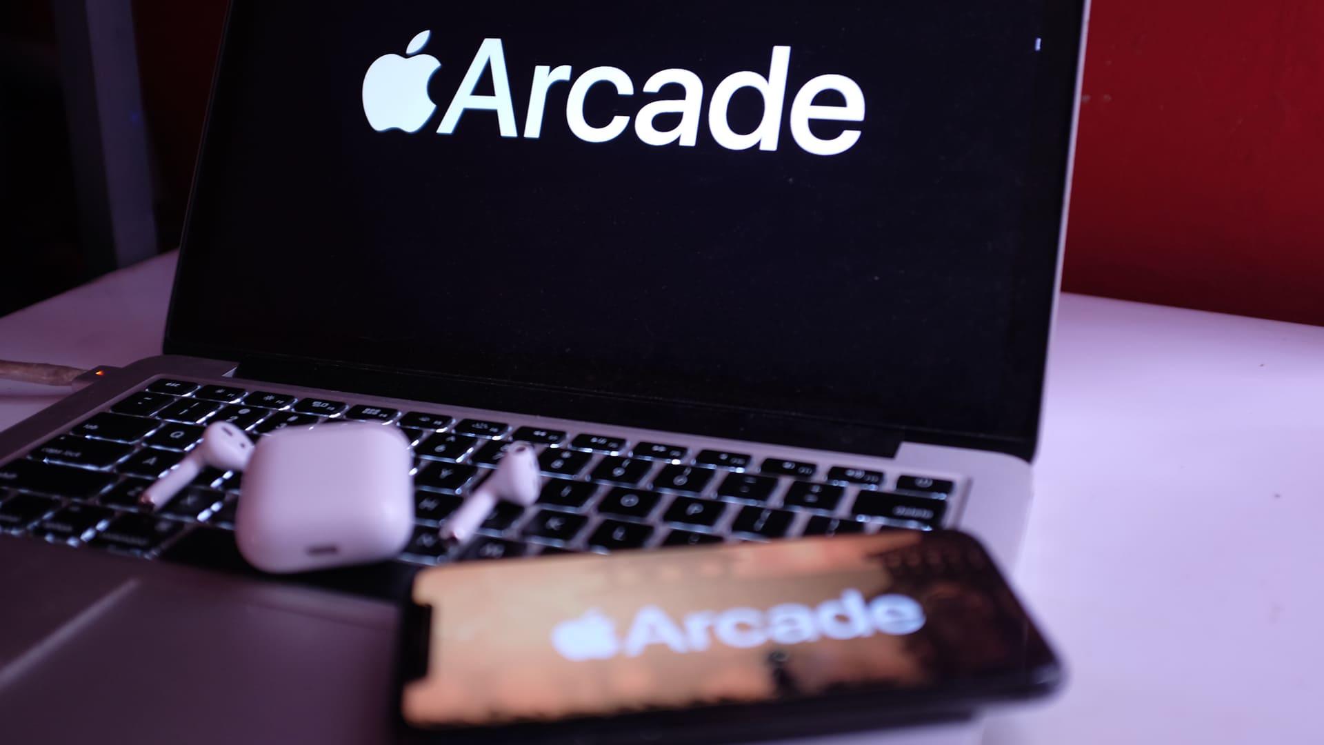 Celular da Apple e Macbook com Apple Arcade na tela