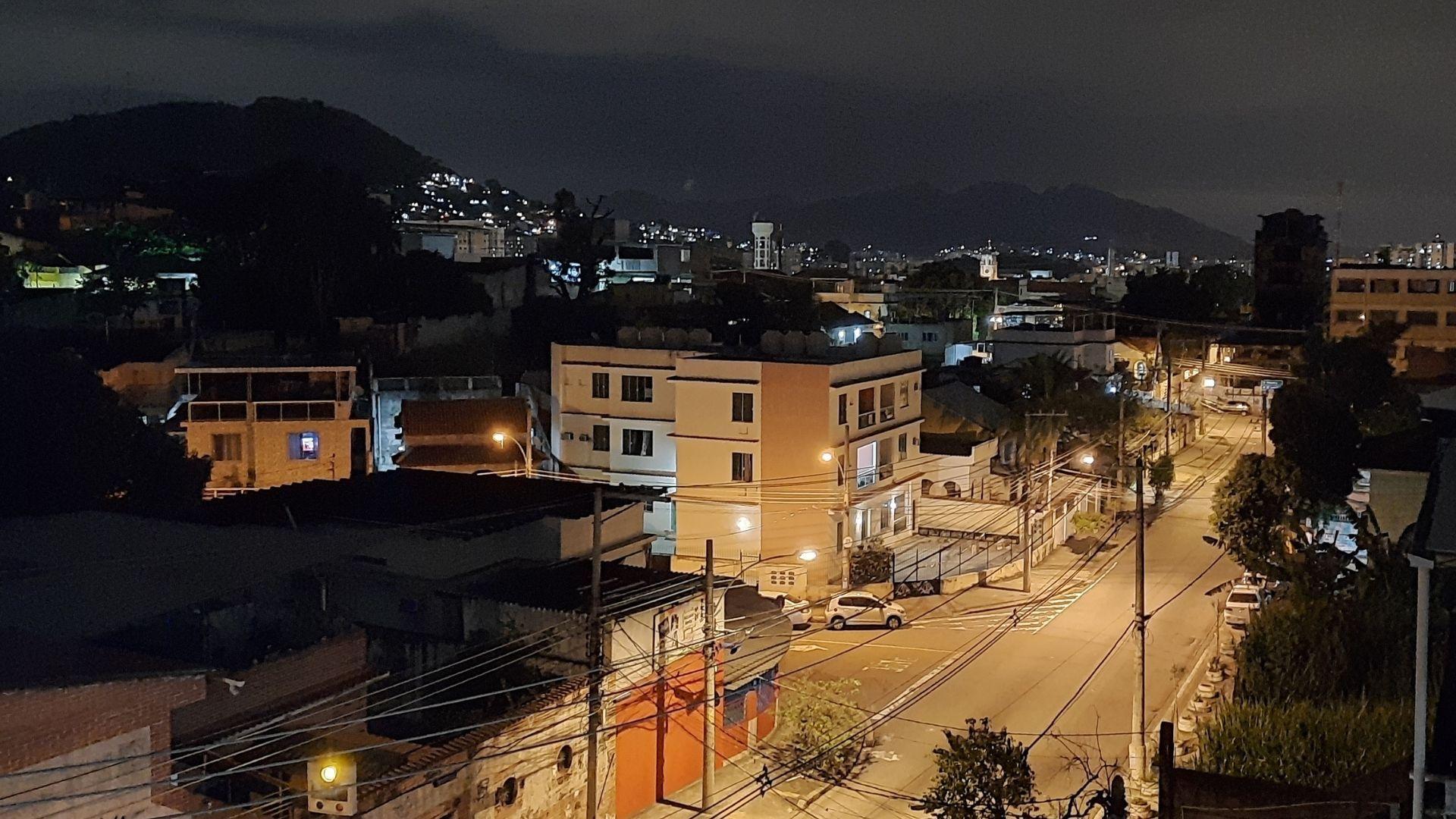 Foto noturna da rua de uma cidade com carros, casas, prédios e o céu ao fundo