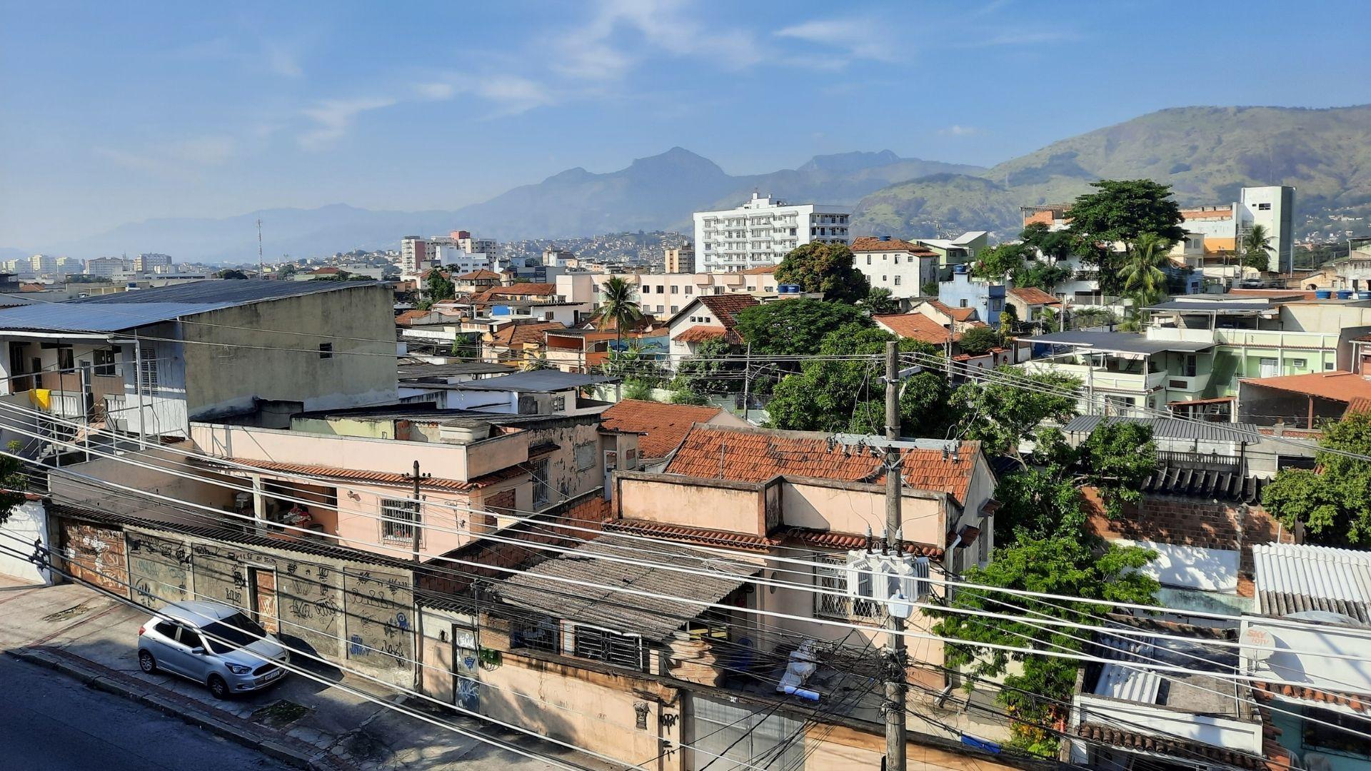 Bairro residencial na cidade com casas, prédios, postes com fios e o céu ao fundo