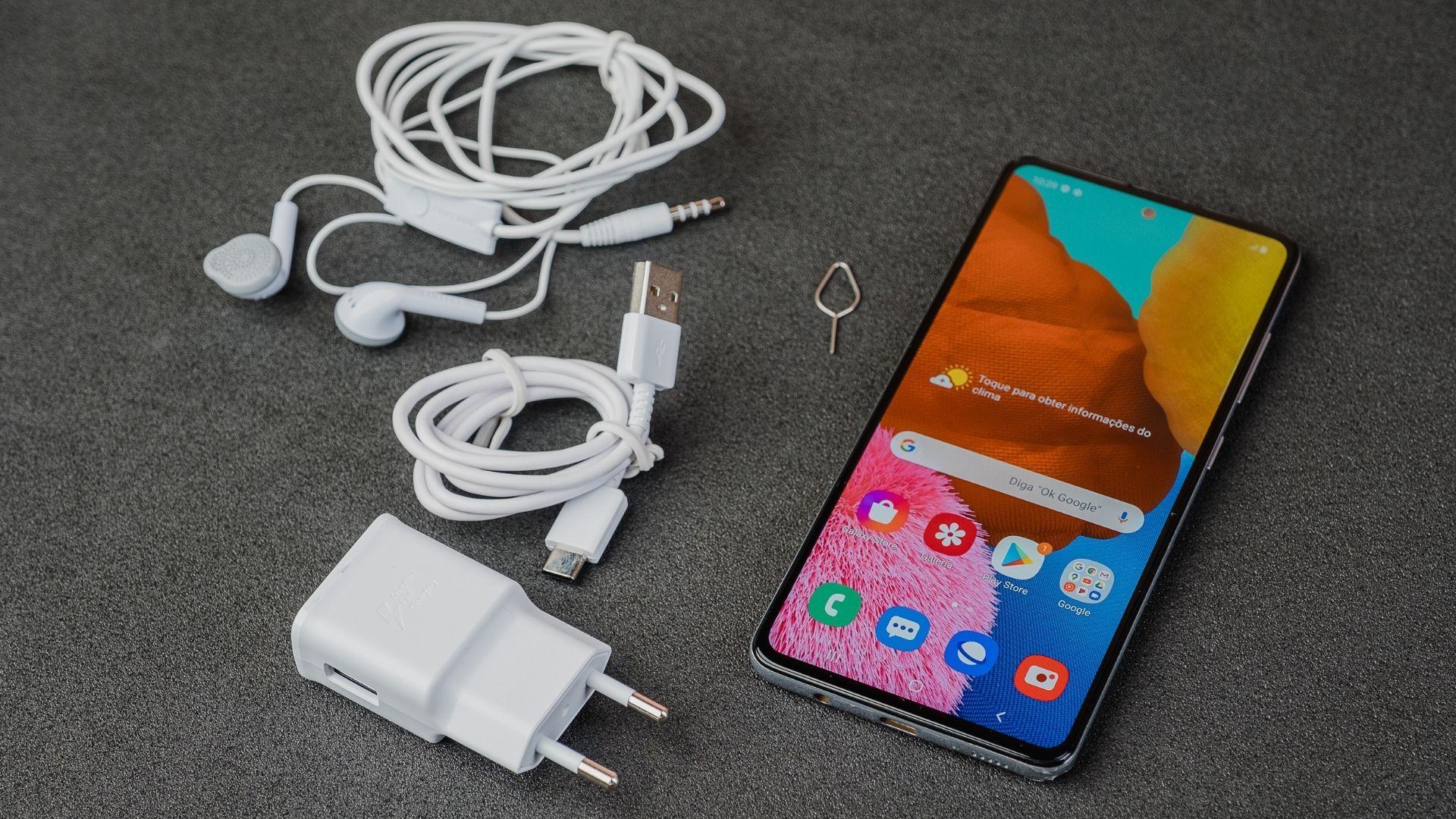 Samsung A51 com a tela acesa ao lado de seus acessórios: fone de ouvido, cabo USB, adaptador de tomada e chave para bandeja do chip