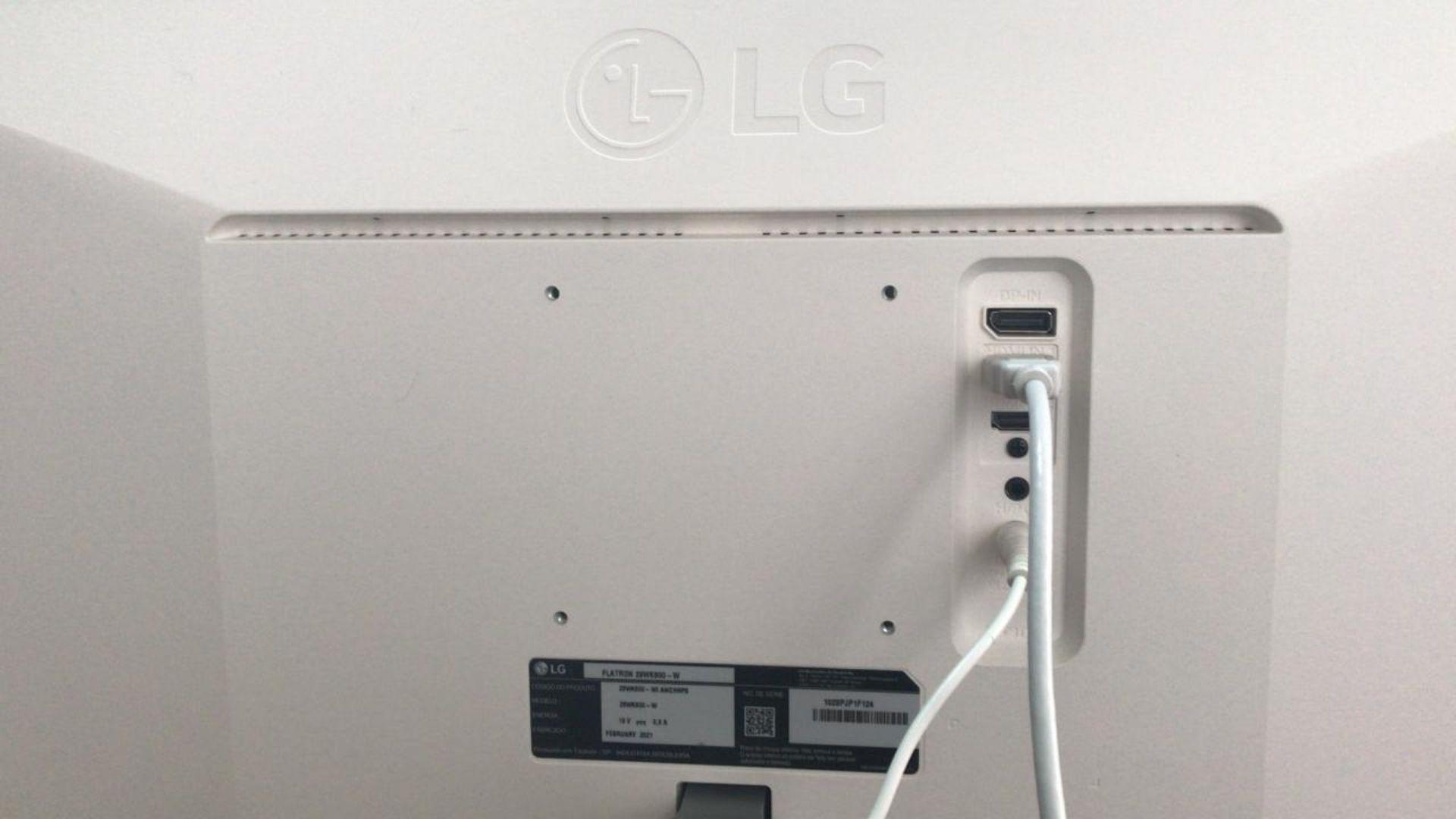 A logo do LG está marcada em relevo na parte de trás. Nessa foto, você também vê o cabo de força e o cabo HDMI conectados às entradas do monitor (Foto: Guilherme Toscano)
