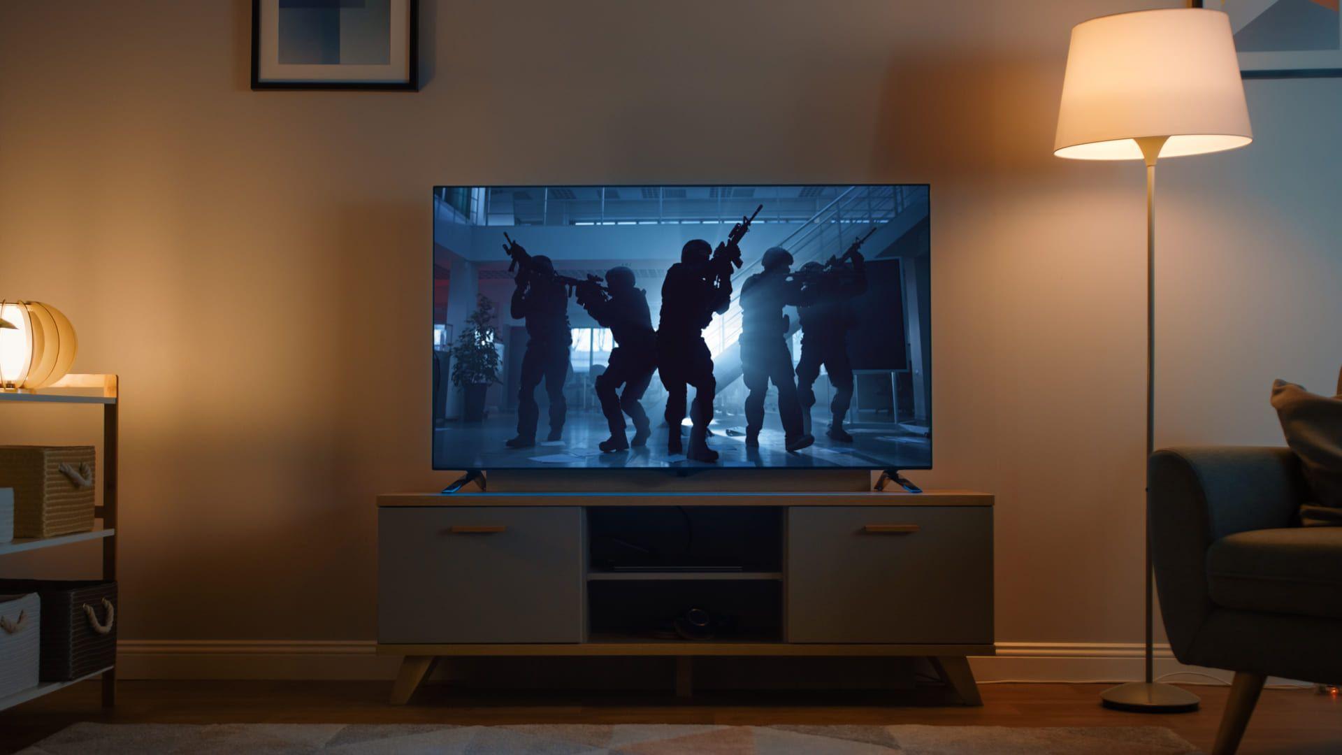 Sala de estar com TV no centro, com soldados armados aparecendo na tela