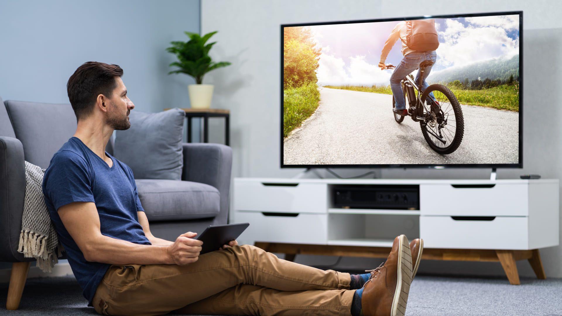 Homem sentado no chão com tablet na mão, olhando para uma TV ao lado
