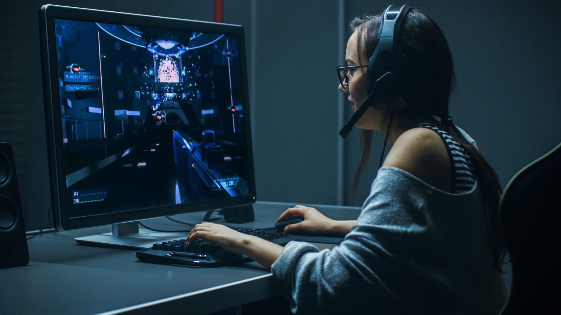 Mulher branca com headset jogando no computador de painel TN