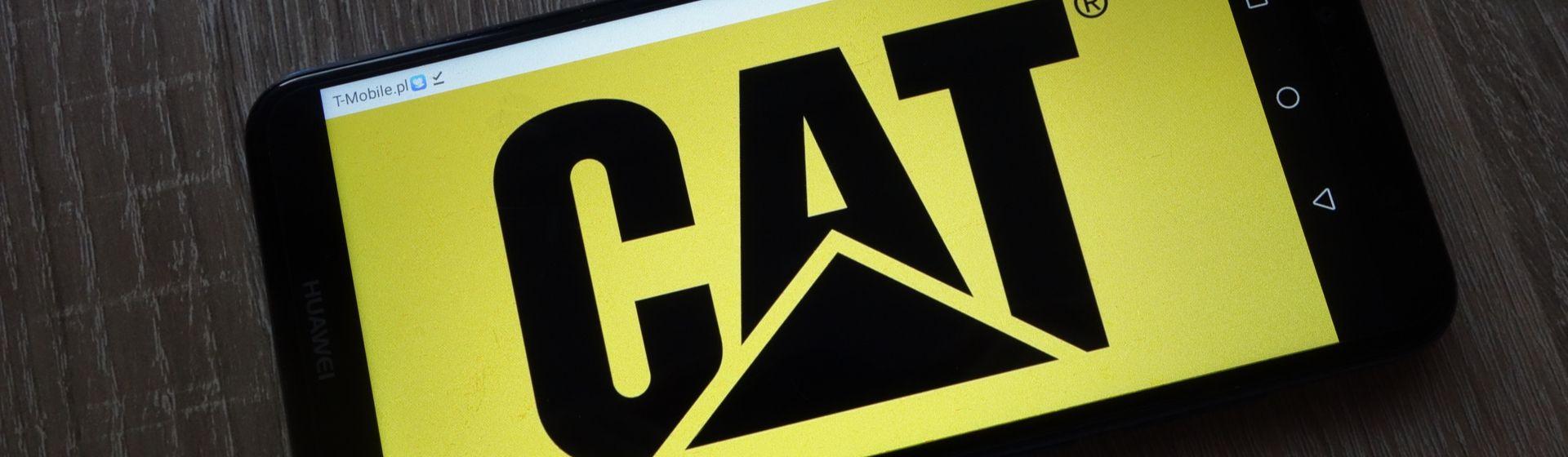 """Celular Caterpillar com marca """"CAT"""" na tela apoiado em cima de mesa de madeira"""