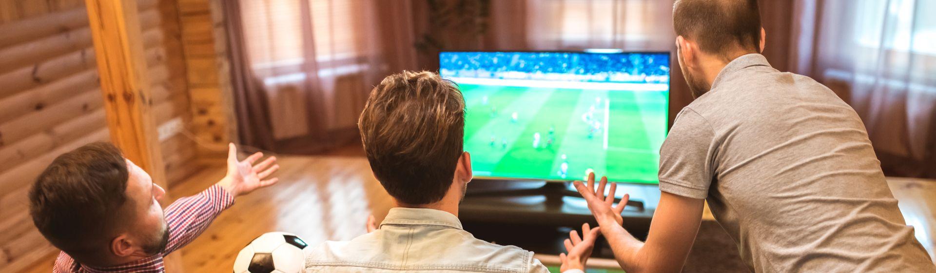 Três homens brancos em frente a uma TV assistindo a um jogo de futebol e torcendo.