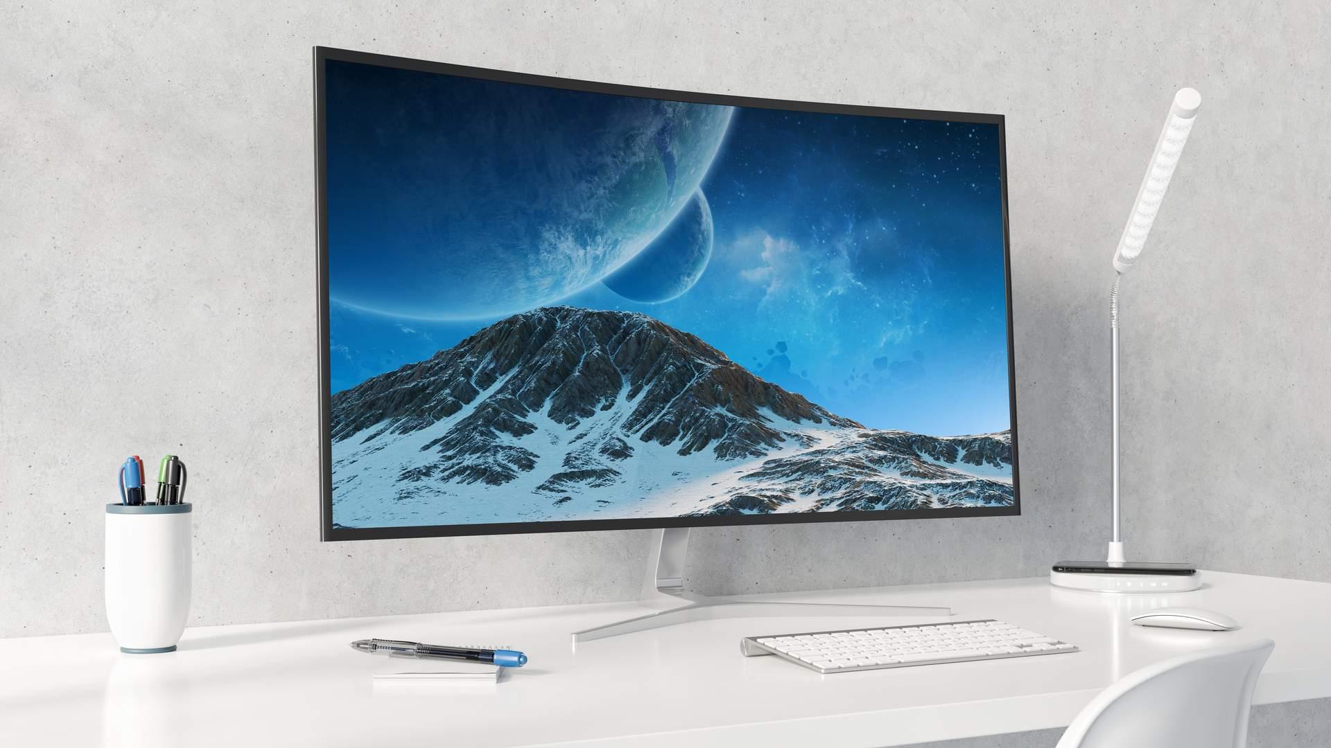 Monitor curvo sobre mesa branco com mini teclado e mouse branco