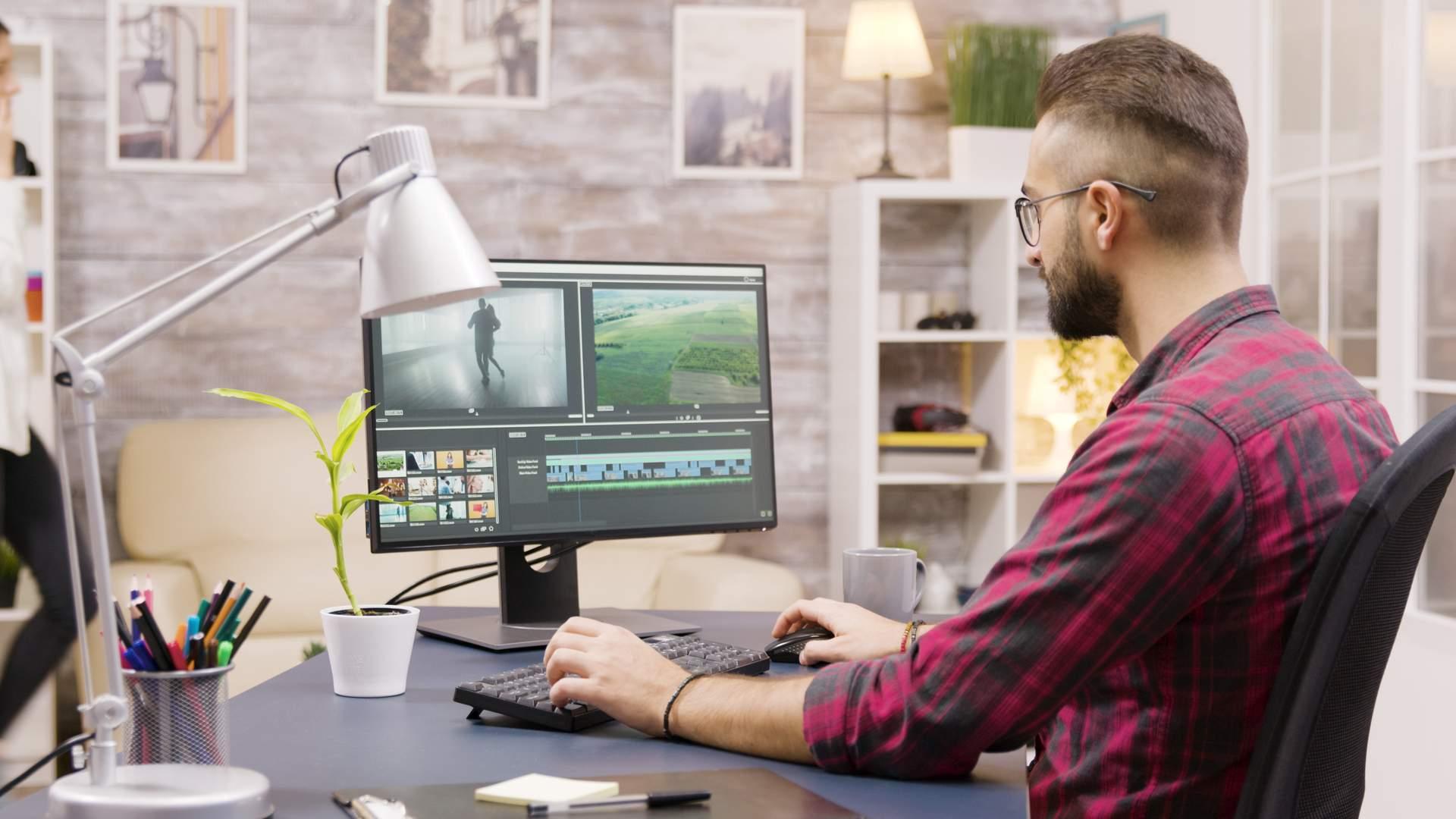Homem branco olhando para tela de monitor enquanto trabalha em edição de vídeo