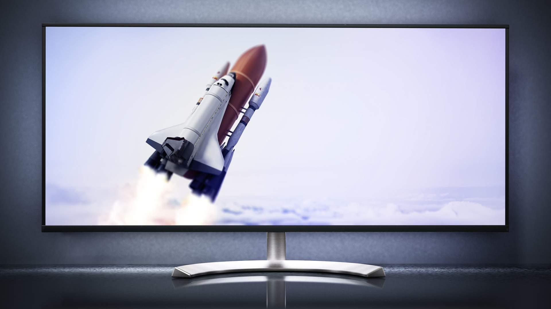 Monitor ultrawide com tela mostrando nave espacial subindo além das nuvens