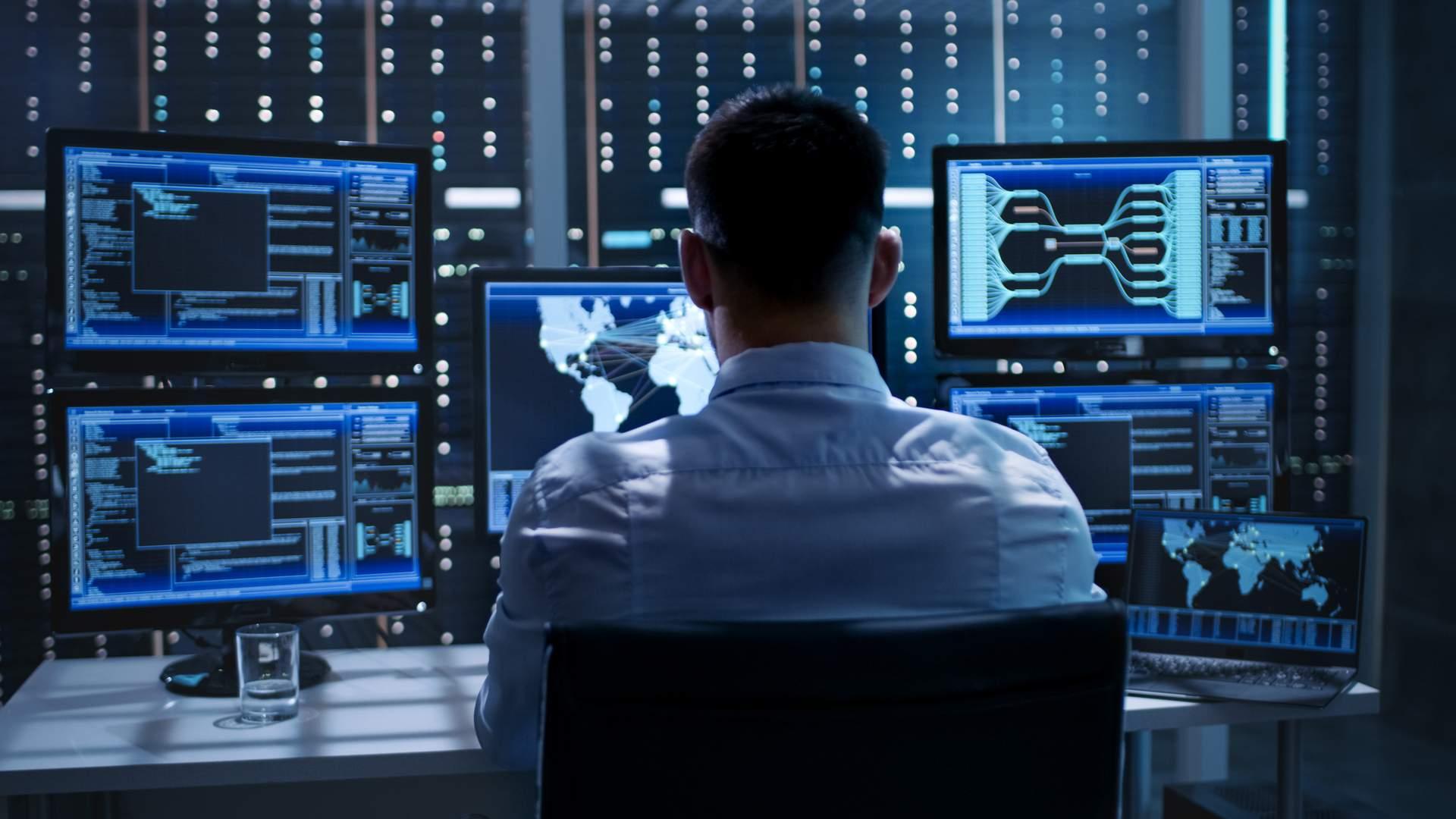 Homem negro com roupa formal olhando para diversas telas de monitor e notebook com gráficos