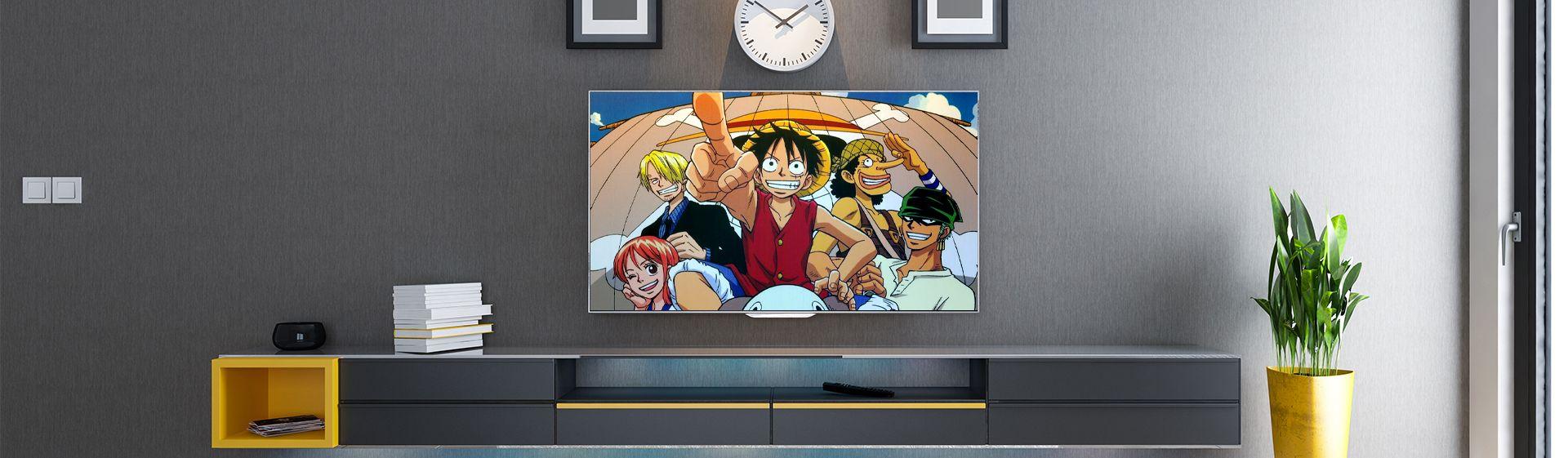 Anime TV passando em uma televisão instalada em parede cinza, com rack cinza e vaso de planta ao lado.
