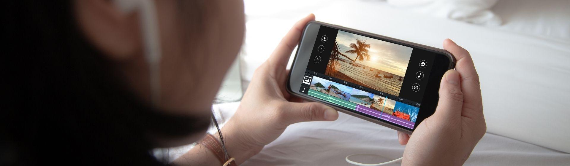 Mulher no canto esquerdo com fone de ouvido segura celular com as duas mãos e vídeo na tela