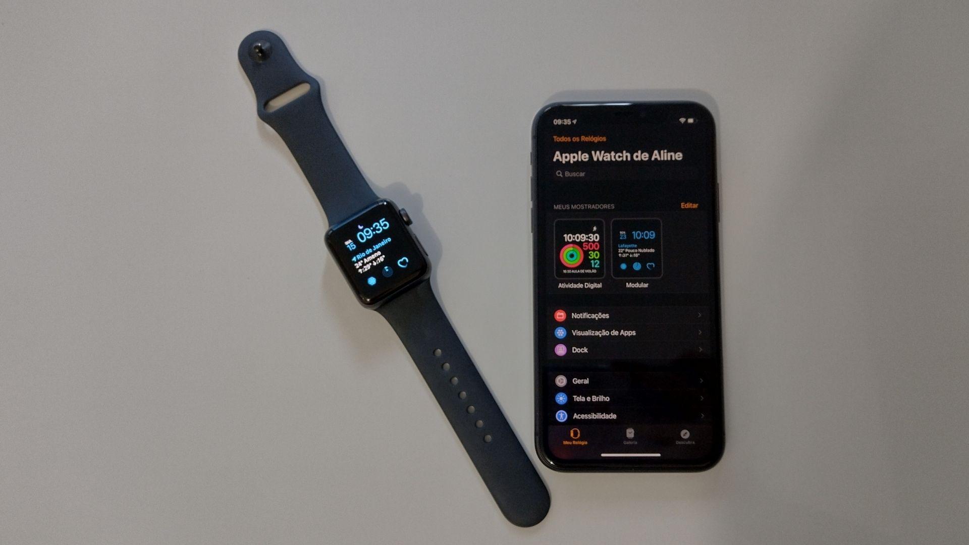 Apple Watch 3 com tela acesa e pulseira de silicone preta ao lado de um iPhone 11 com tela acesa e app Watch aberto em um fundo branco