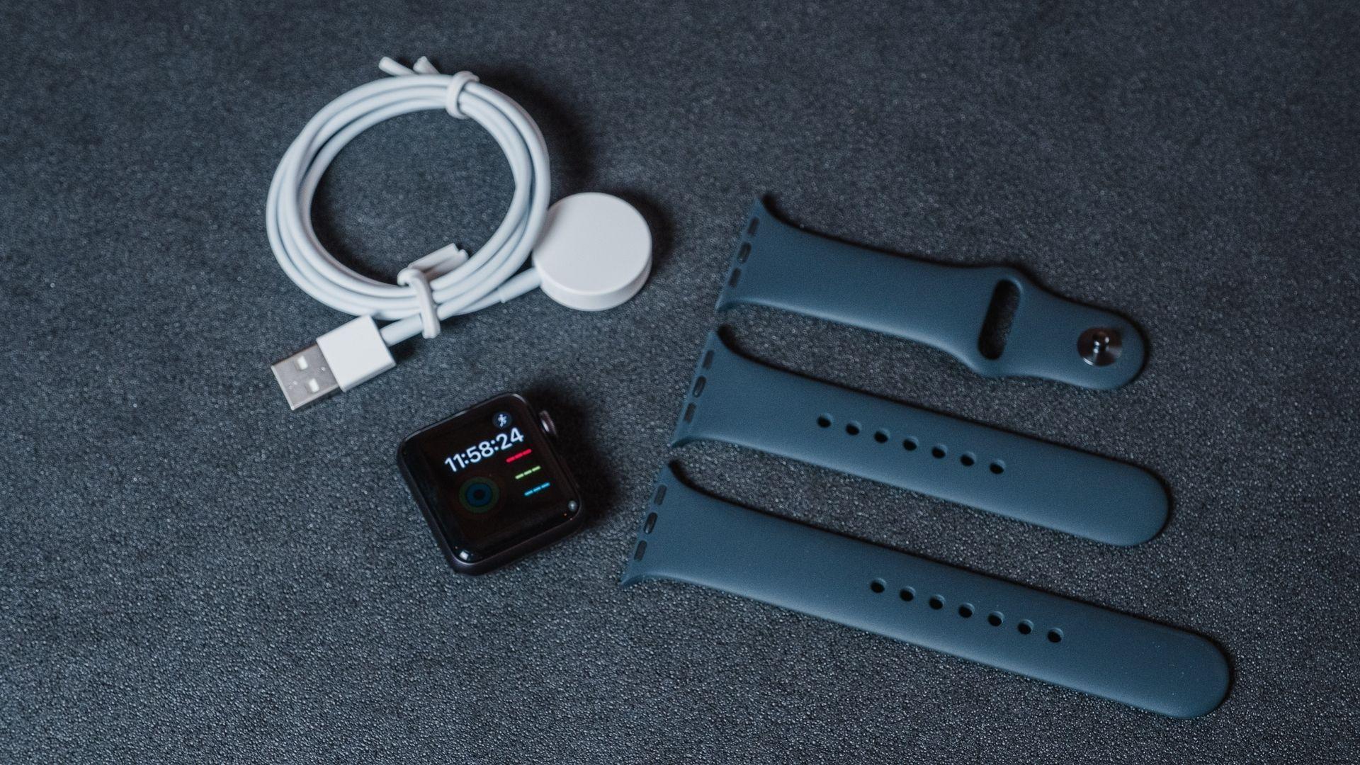 Caixa, pulseiras e carregador do Apple Watch 3 em um fundo cinza