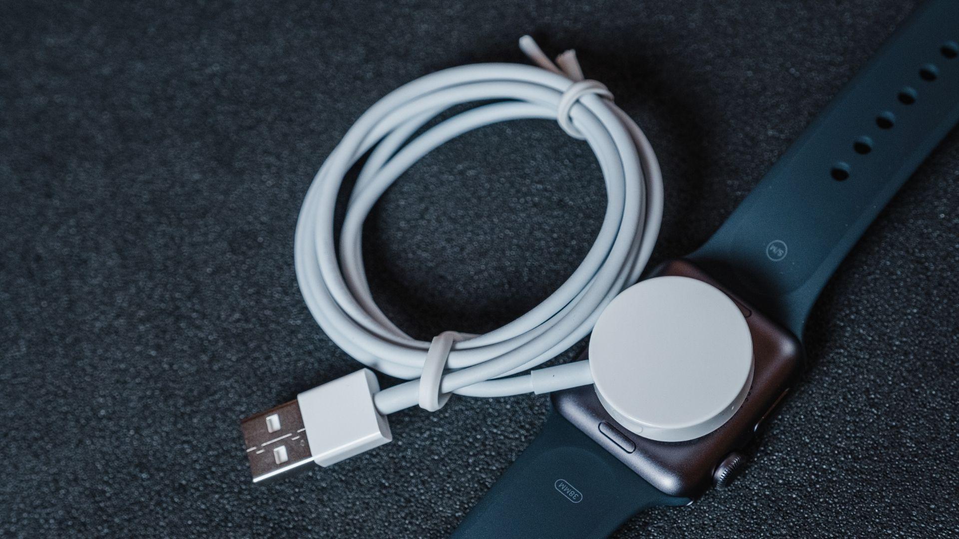 Carregador magnético do Apple Watch 3 conectado ao relógio em um fundo cinza