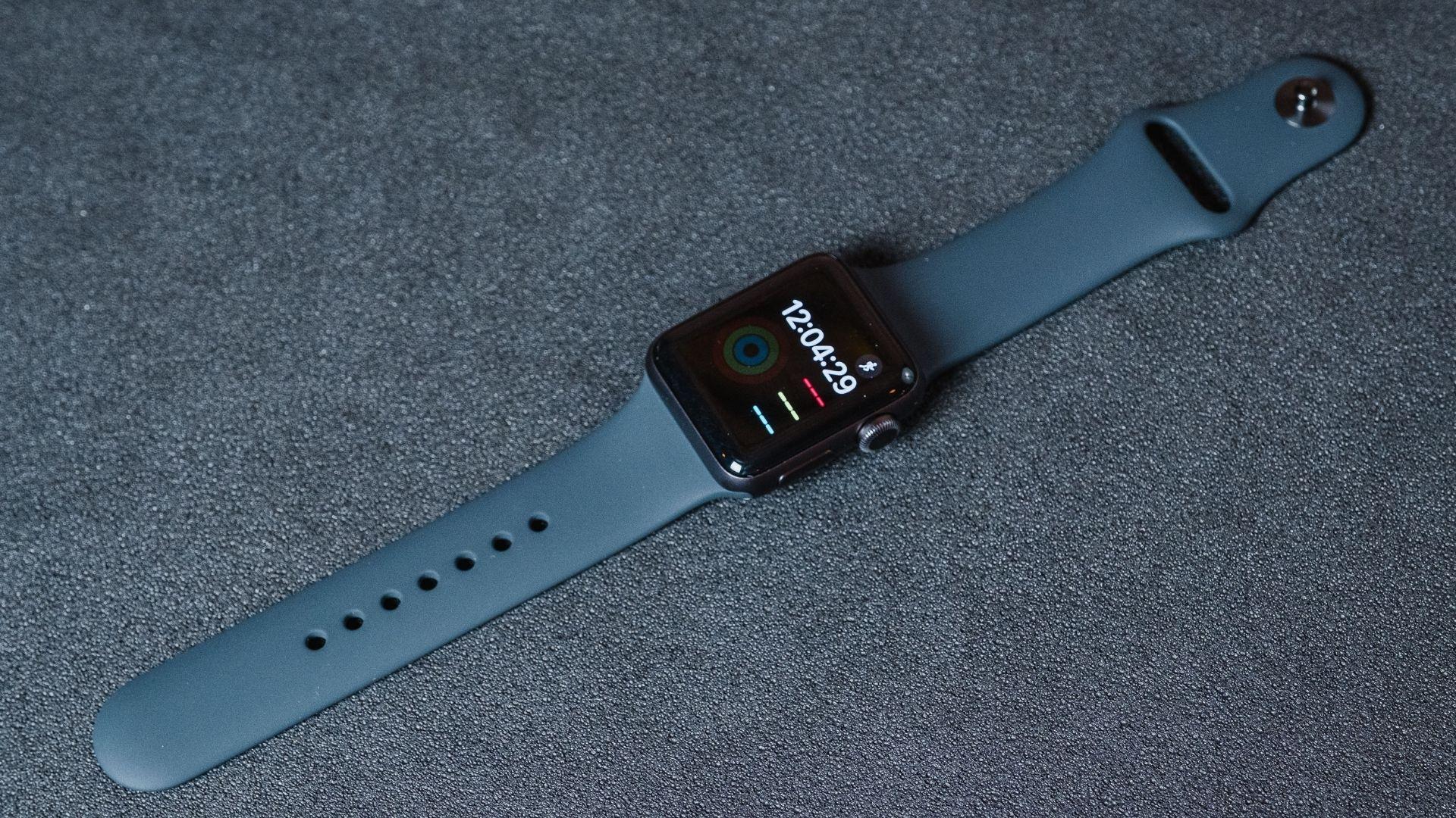 Apple Watch 3 com a tela acesa mostrando a hora e pulseira de silicone preta em um fundo cinza