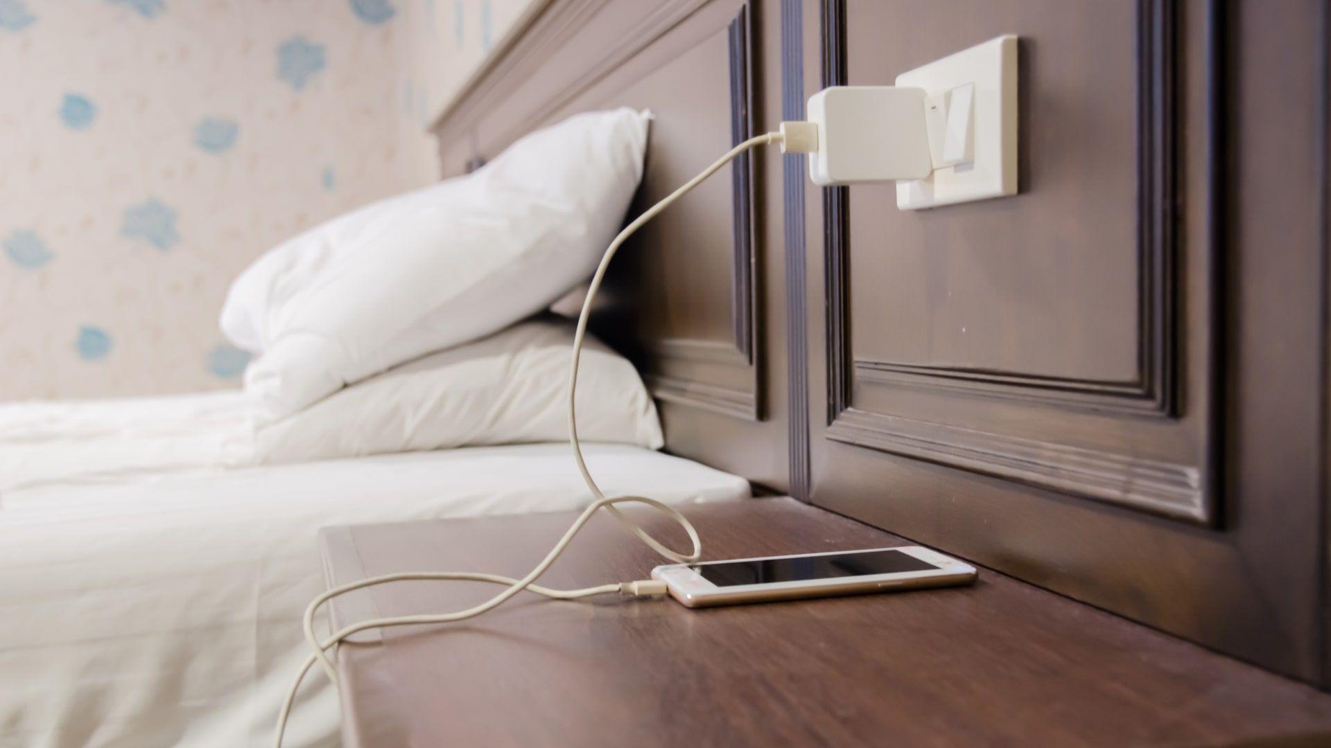Celular carregando em uma mesa de cabeceira, ao lado de uma cama