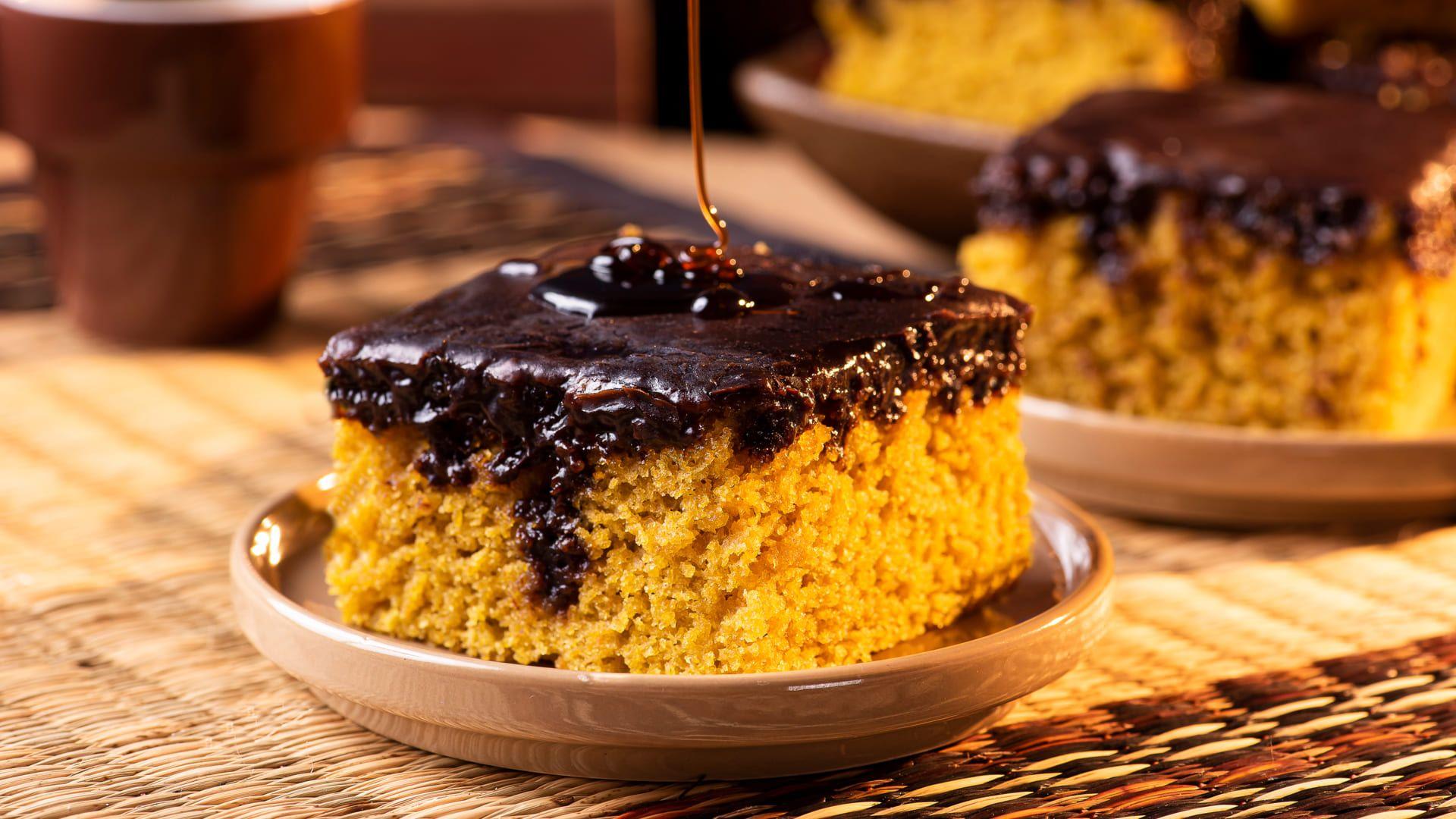 Pedaço de bolo de cenoura com calda de chocolate em um prato em cima da mesa.