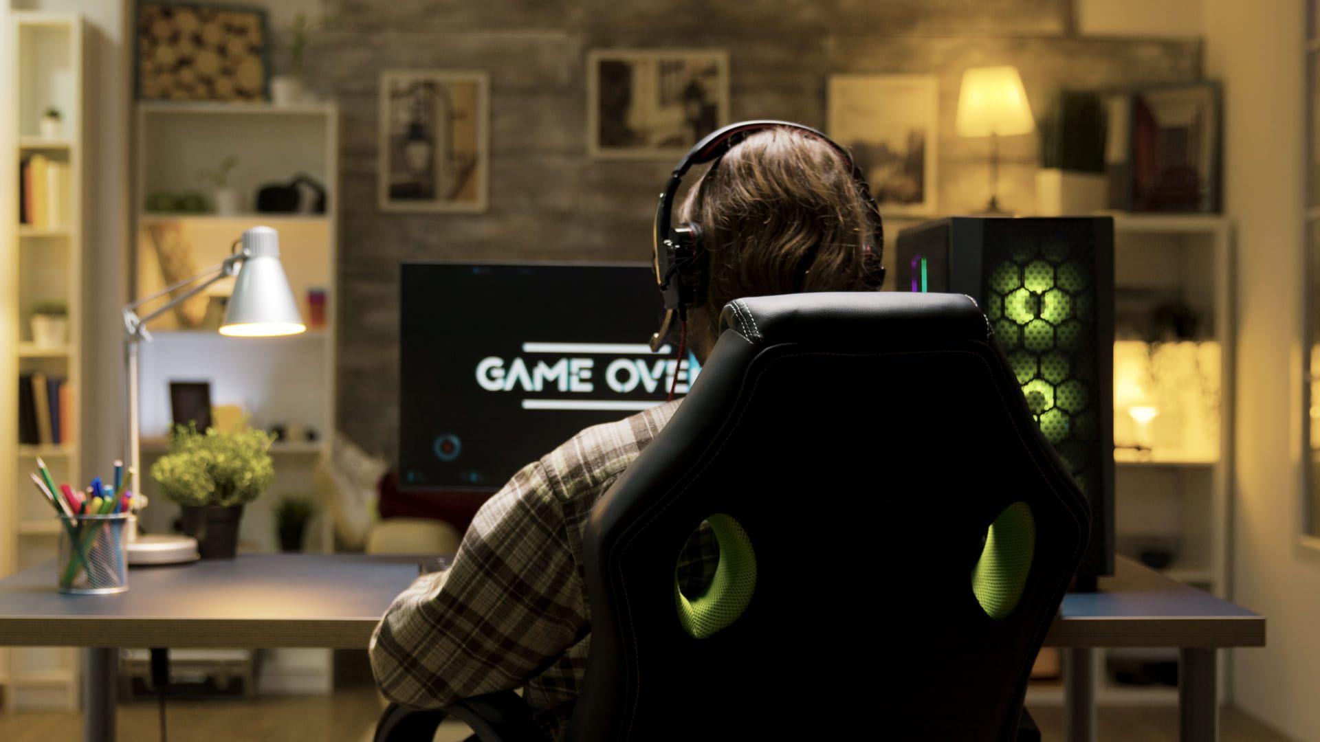 Jovem sentado em cadeira gamer jogando de frente para o computador e de costas para a foto.