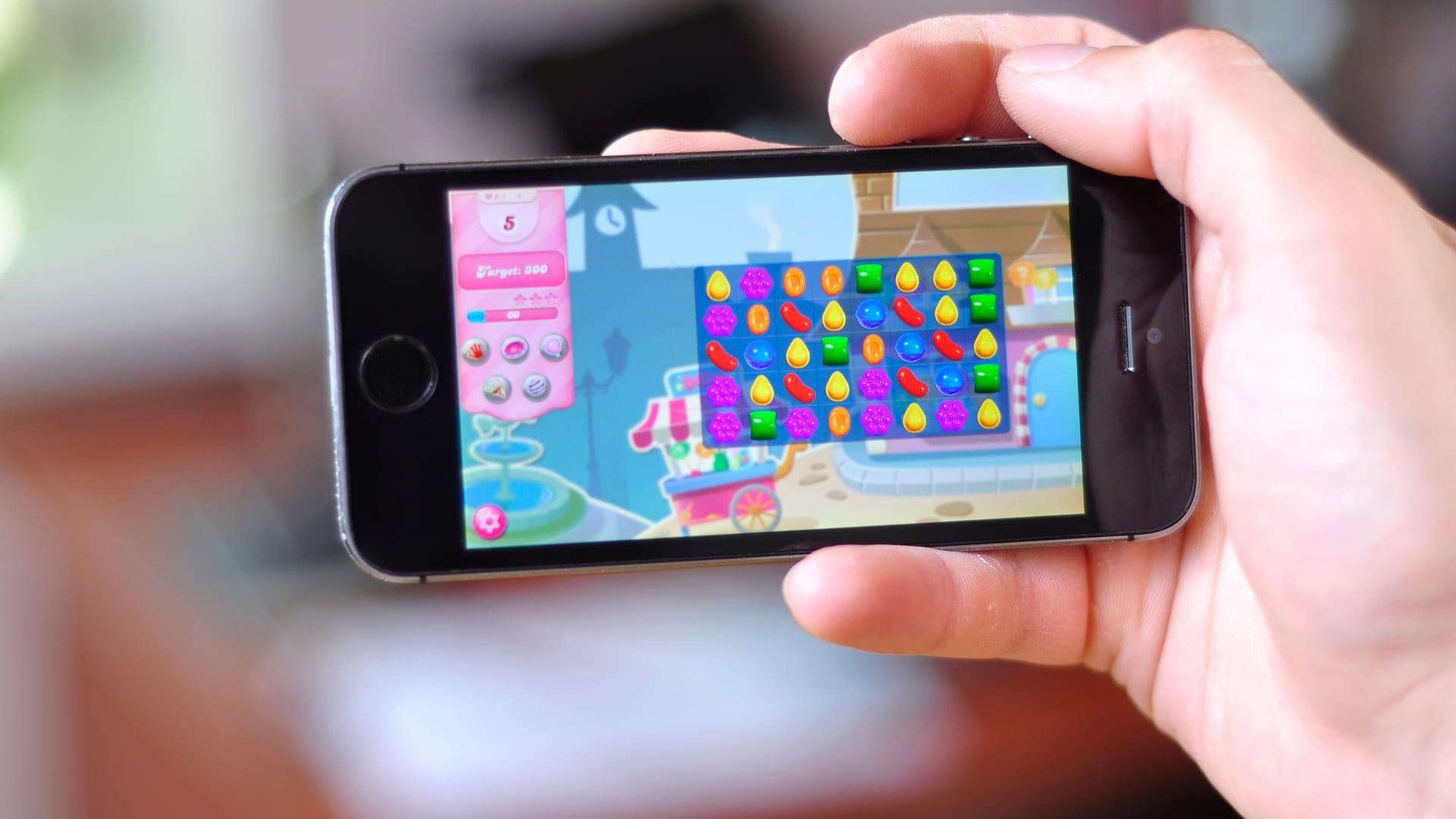 Mão segurando celular com Candy Crush rodando na tela