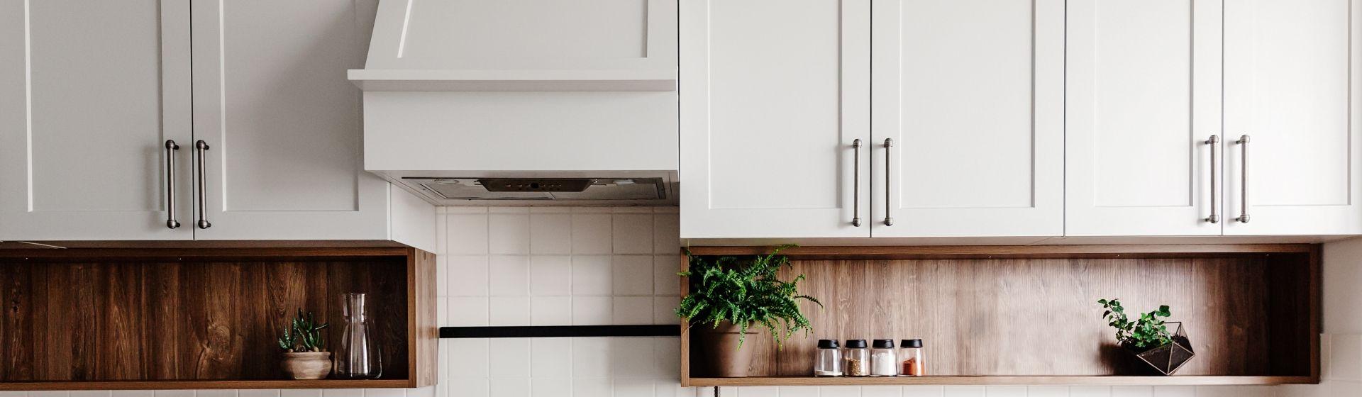 Armários de cozinha superiores brancos com puxadores pretos em cima de nichos de madeira com plantas e temperos