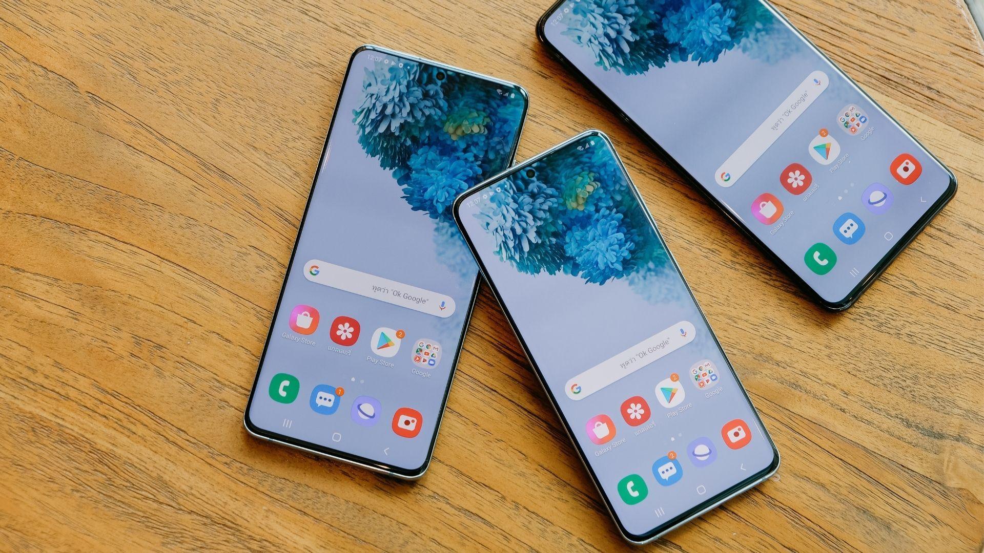 Três celulares Samsung com tela inicial aparecendo apoiados em fundo de madeira