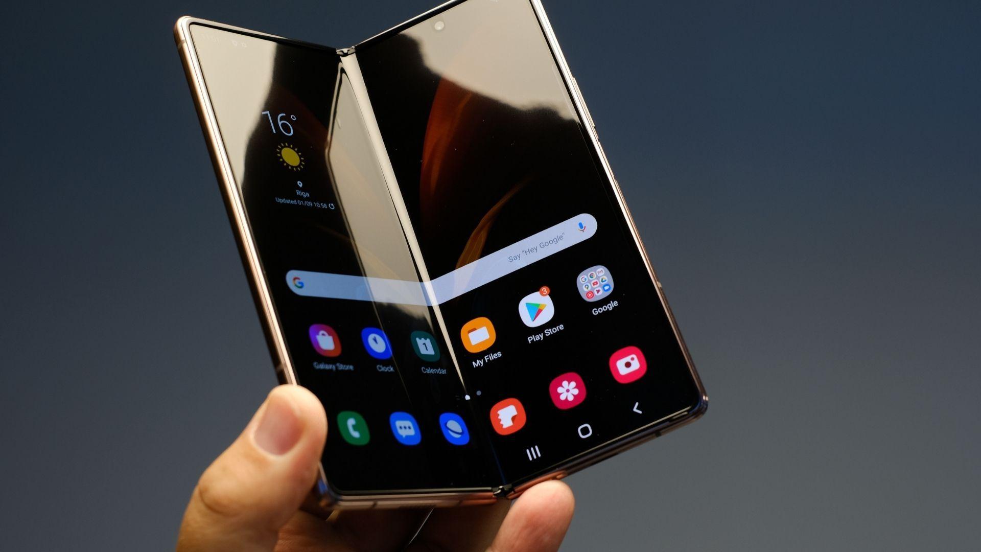 Celular Samsung dobrável sendo segurado por uma mão em fundo cinza