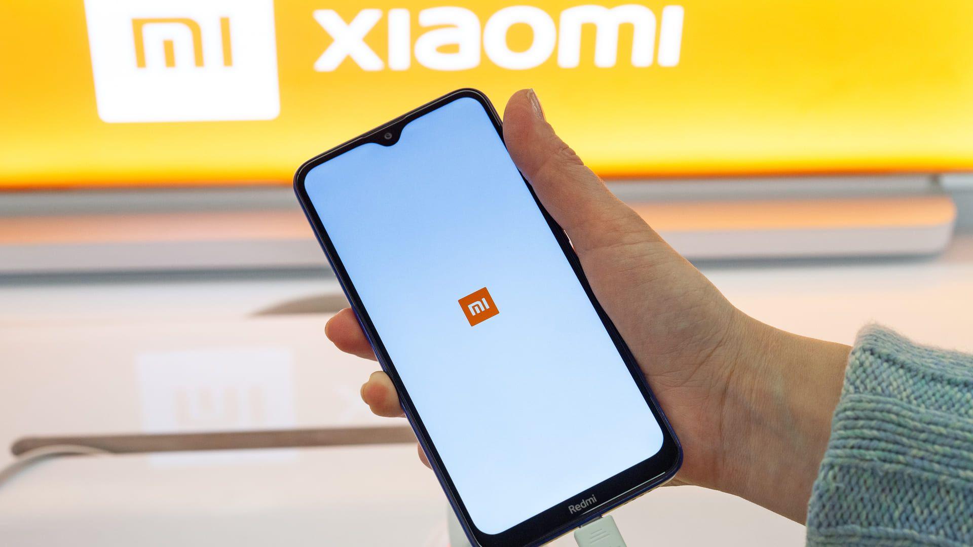 """Mão segurando celular Xiaomi com o símbolo """"Mi"""" ao fundo"""