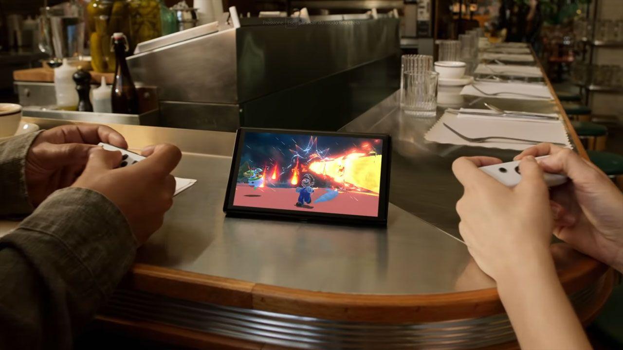 Nintendo Switch OLED no centro, com jogo na tela e duas mãos segurando os controles enquanto jogam.