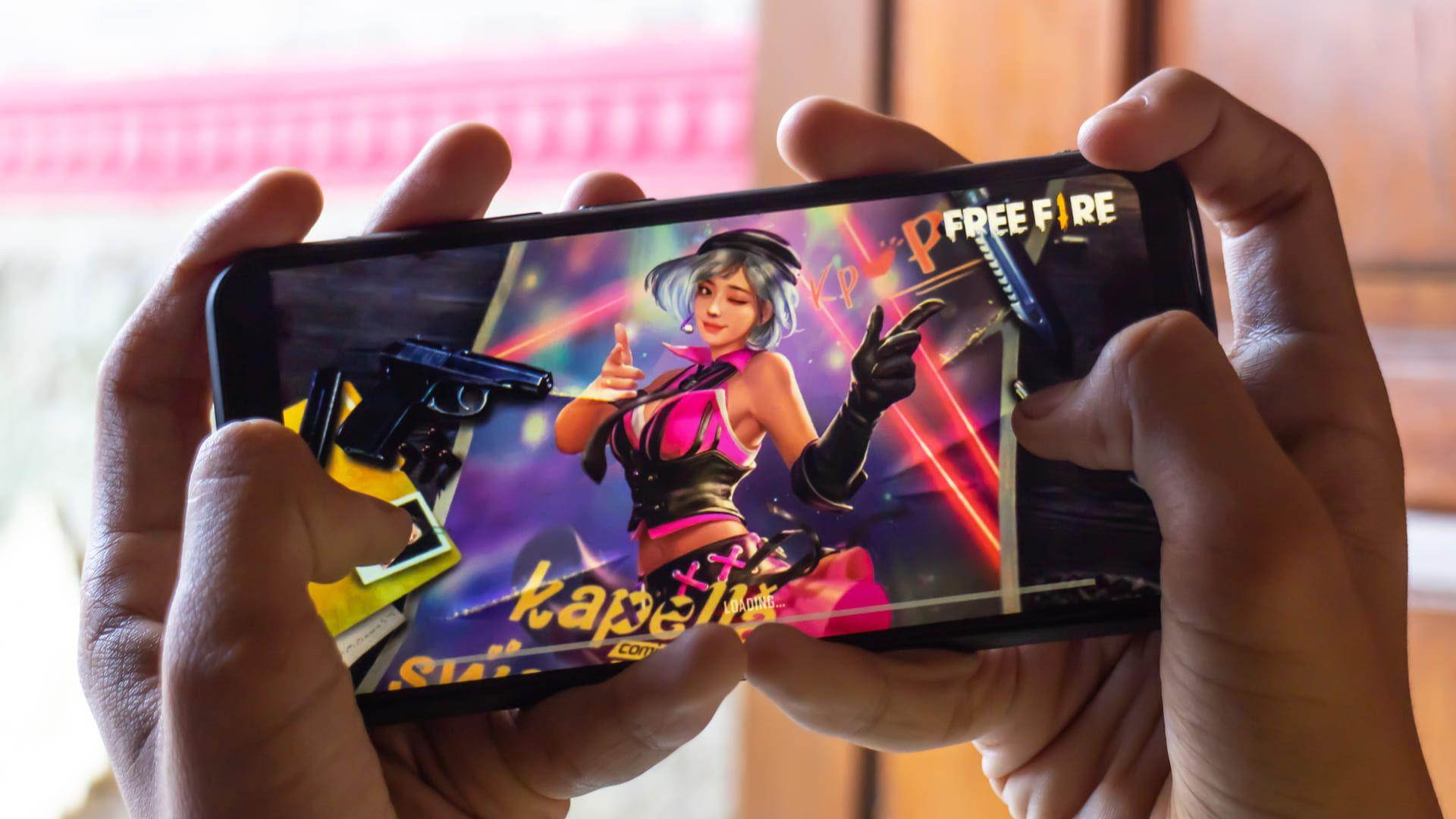 Mãos segurando celular com o jogo Free Fire Max aberto