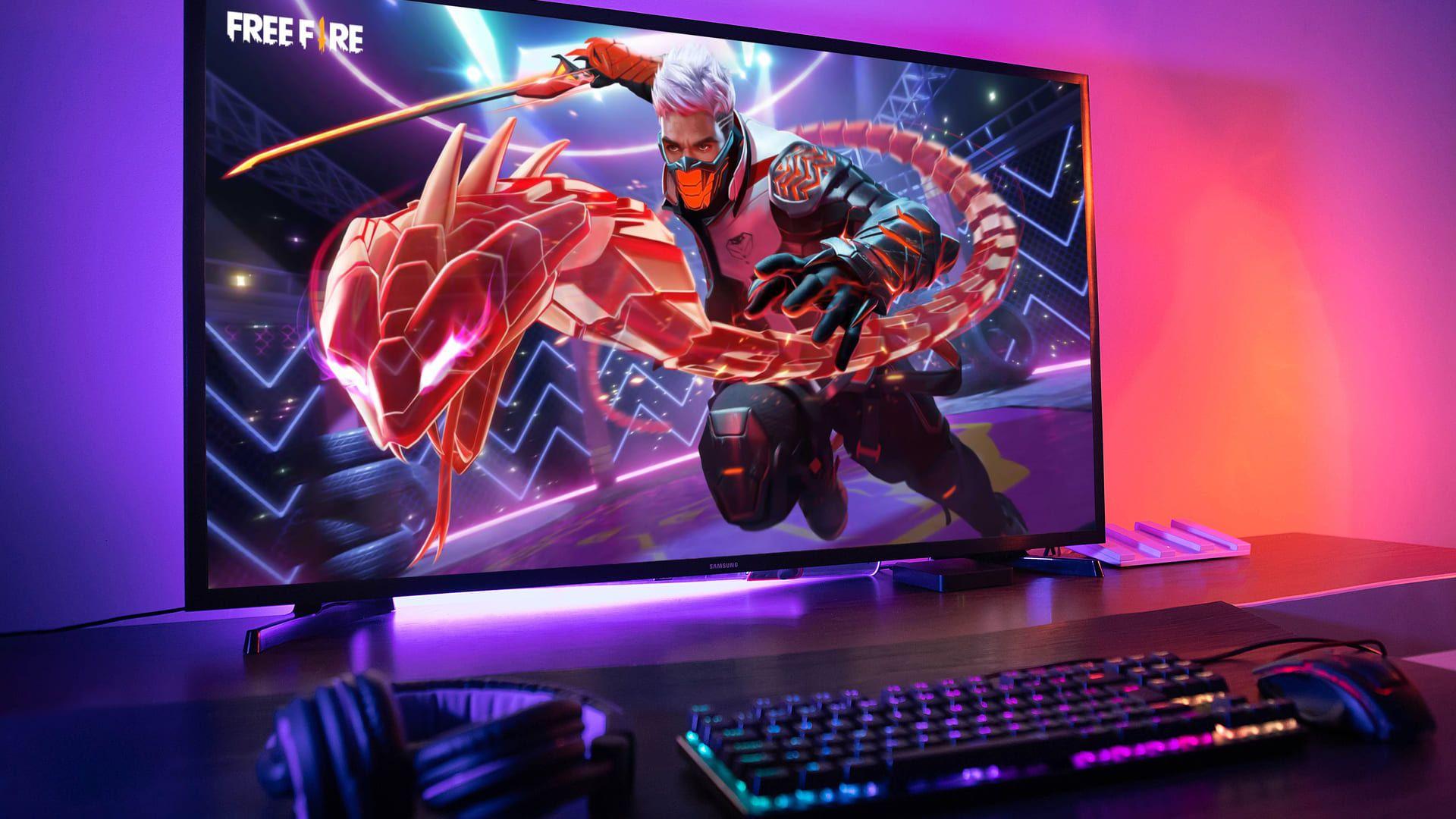 Mesa com computador montado e monitor exibindo o jogo Free Fire Max