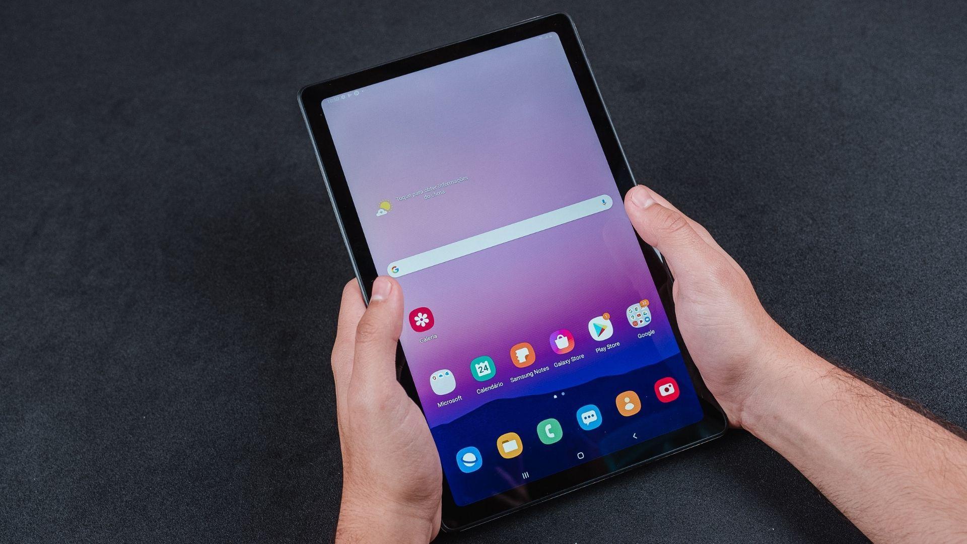 Galaxy Tab A7 na vertical e com tela acesa sendo segurado por duas mãos